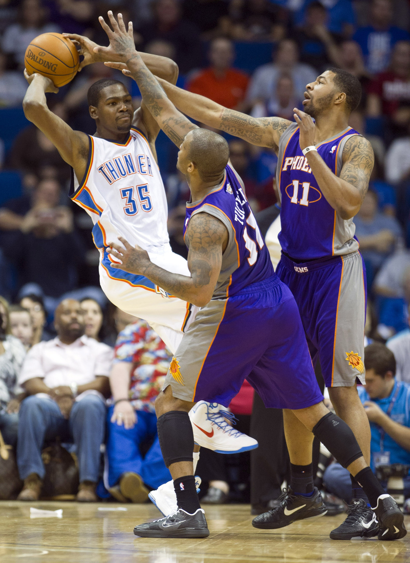 Tulsa, OK, USA; Oklahoma City Thunder forward Kevin Durant (35) looks to make a pass under pressure from Phoenix Suns forward P.J. Tucker (17) and forward Markieff Morris (11) during the first half of a game at the BOK Center. Thunder defeated the Su