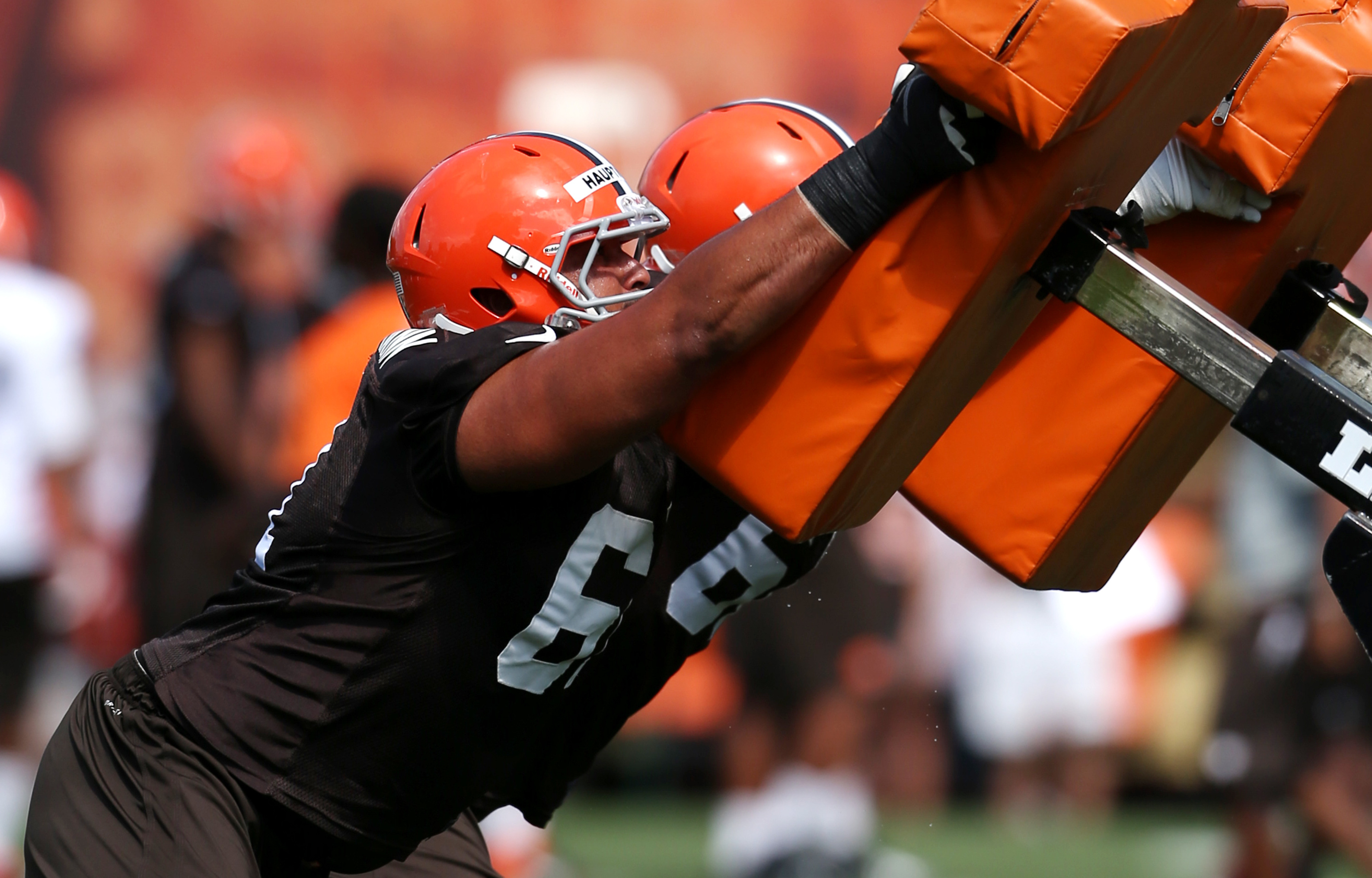 Cleveland Browns offensive linesman Caylin Hauptmann (61), left, and offensive linesman Ryan Miller (60) hit the sled during training camp at the Cleveland Browns Training Facility on Friday. Miller got hurt when practice moved indoors on Saturday.
