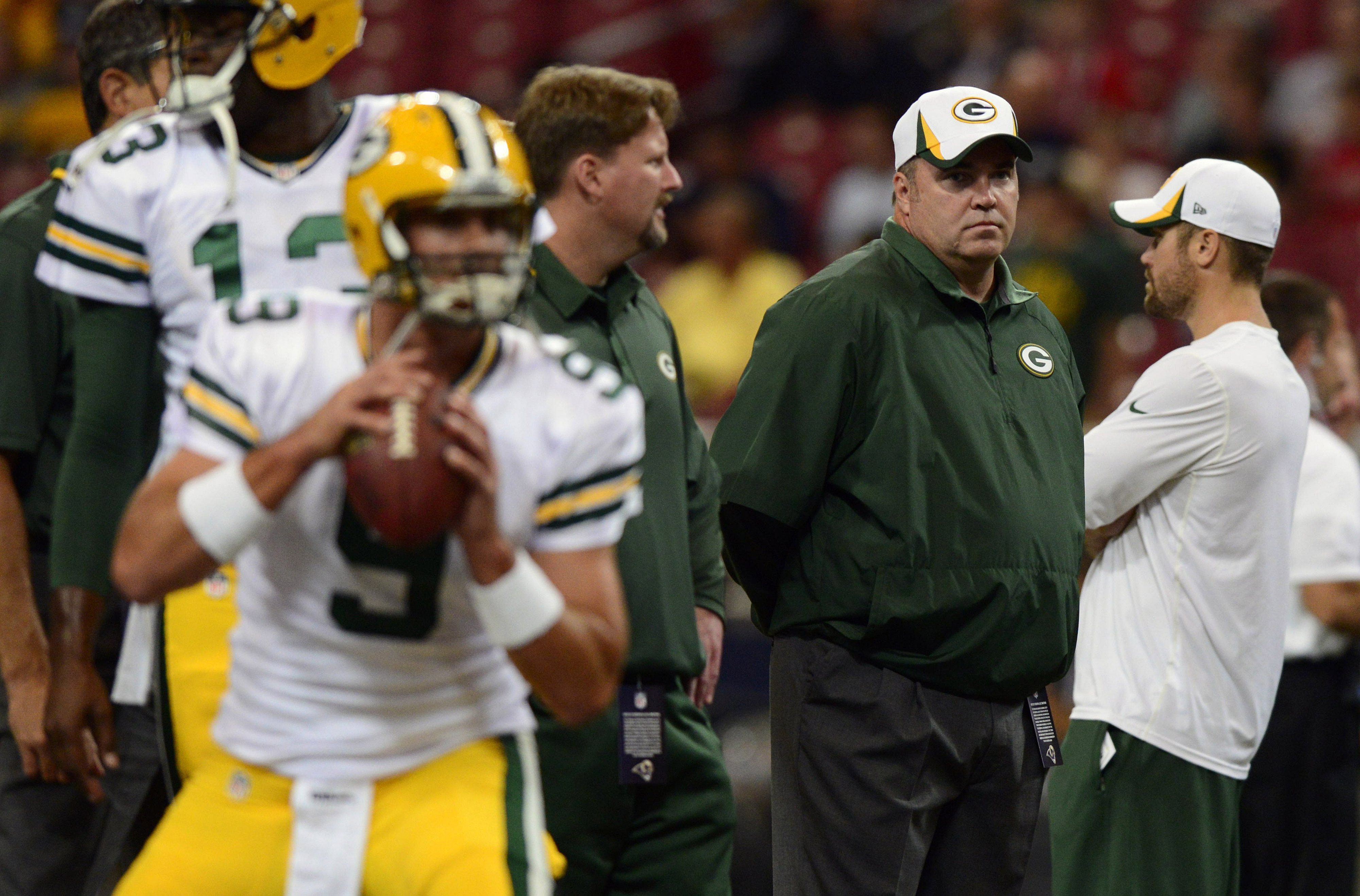 Coach McCarthy looks on as B.J. Coleman (9) and Vince Young (13) warm up before the Packers preseason game against the Rams on August 17th