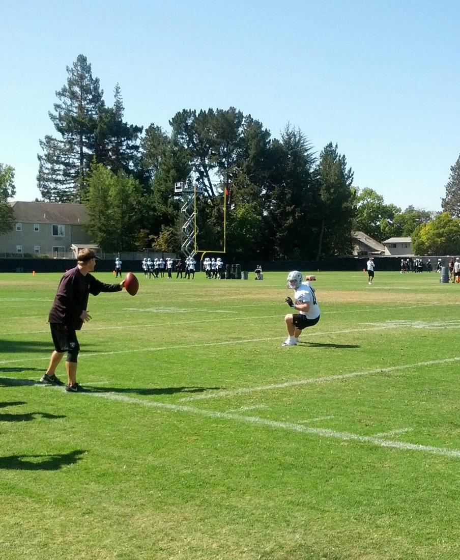 Oakland Raiders defensive coordinator, Jason Tarver, works with linebacker Chase Thomas at 2013 training camp