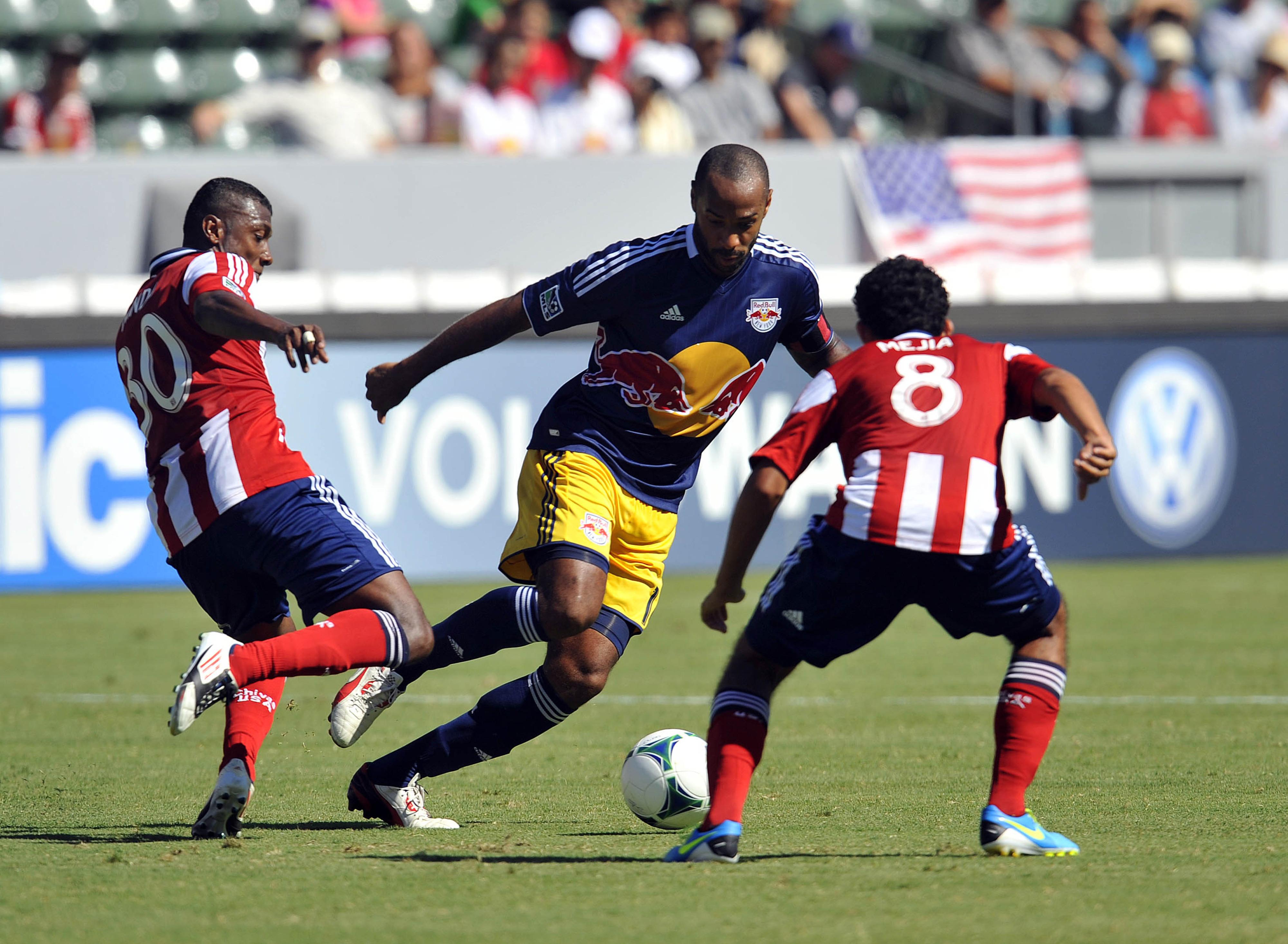 Midfielders Oswaldo Minda and Edgar Mejia disrupt Thierry Henry