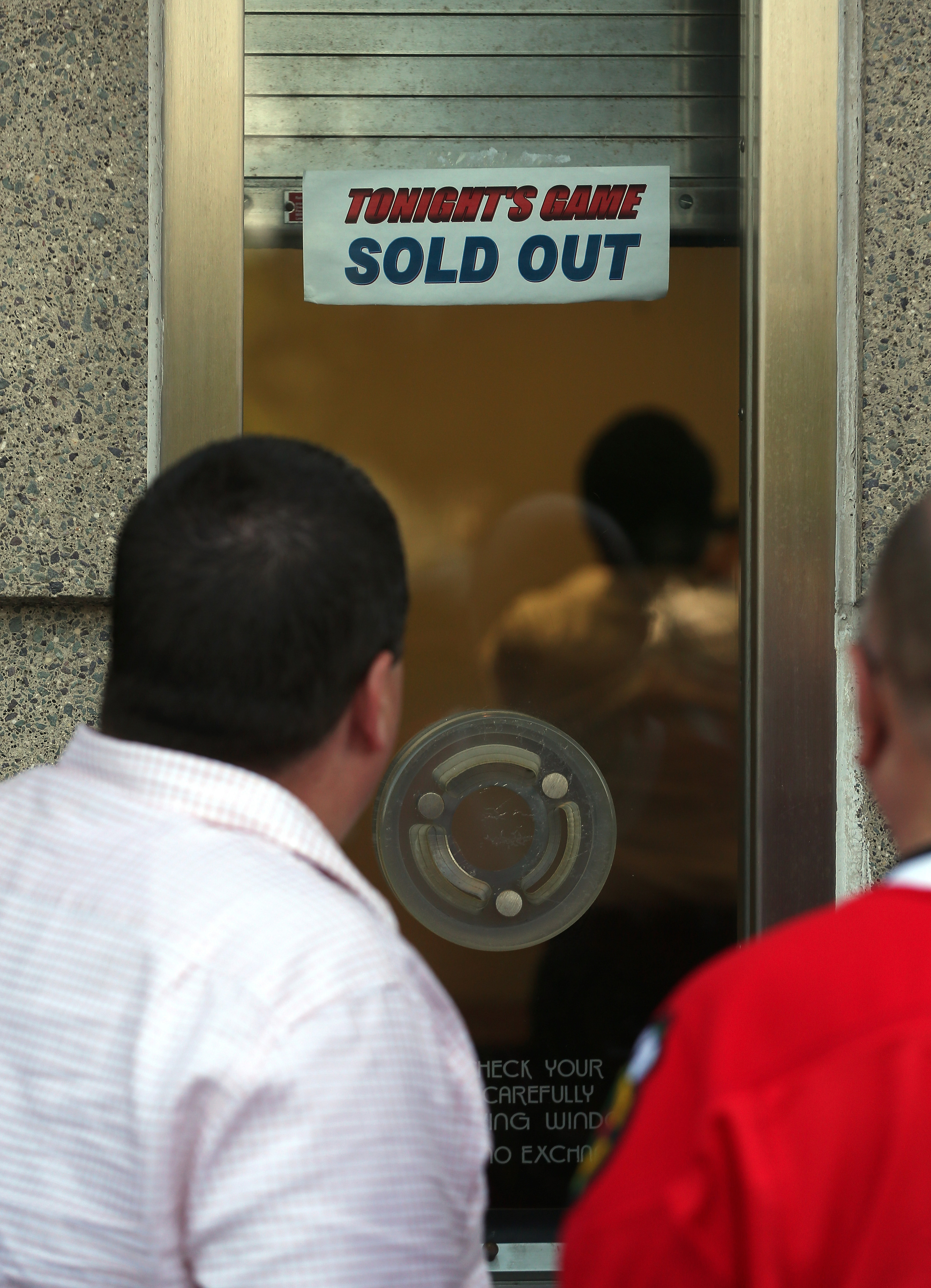 """CHICAGO, IL - JUNE 15: A sign which reads """"Tonight's Game Sold Out"""" as fans stand outside the ticket window prior to Game Two of the NHL 2013 Stanley Cup Final between the Chicago Blackhawks and the Boston Bruins at United Center on June 15, 2013."""