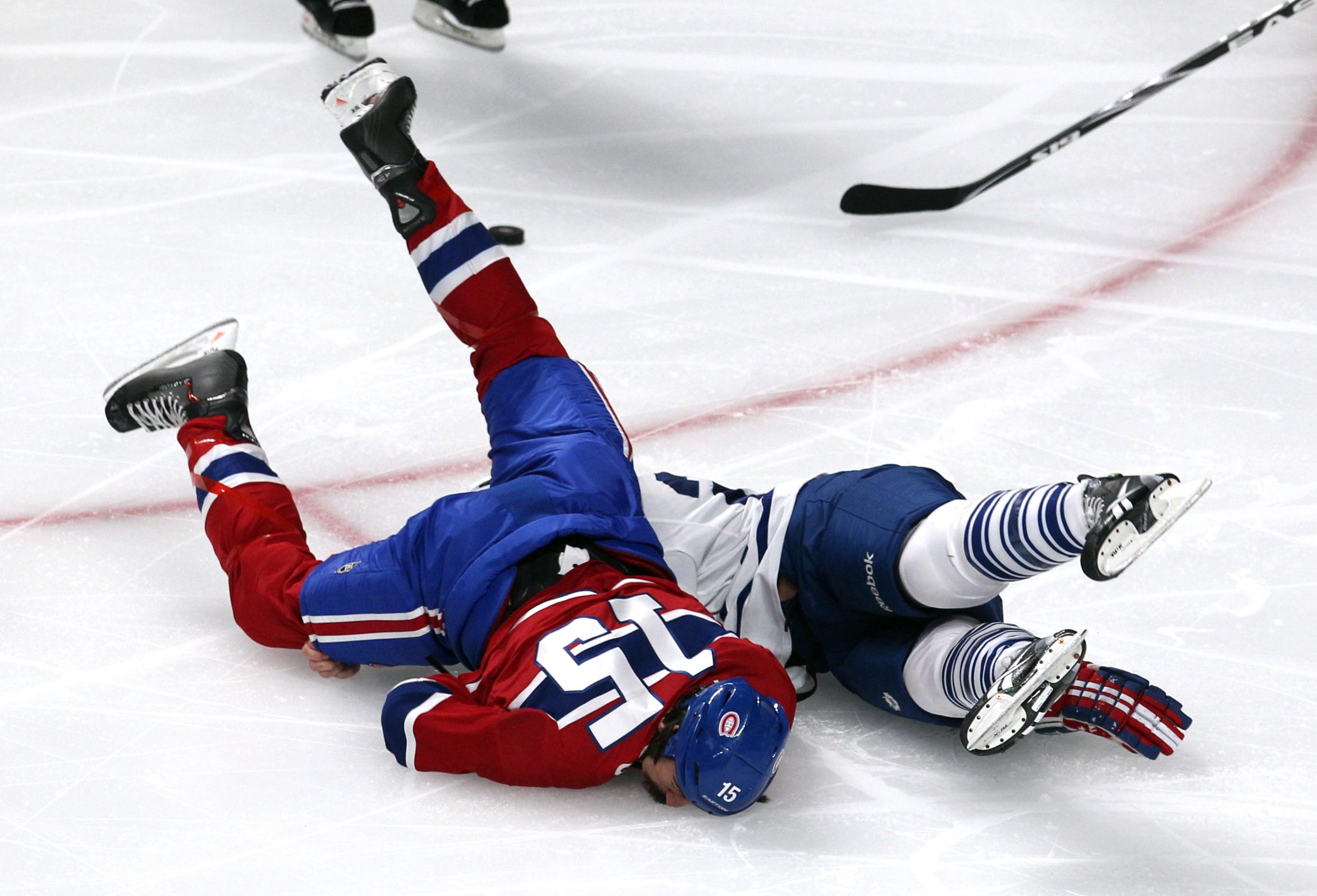 Montreal Canadiens right wing George Parros (15) hits his head on the ice as he fights with Toronto Maple Leafs right wing Colton Orr (28) during the third period at Bell Centre. Mandatory Credit: Jean-Yves Ahern-USA TODAY Sports