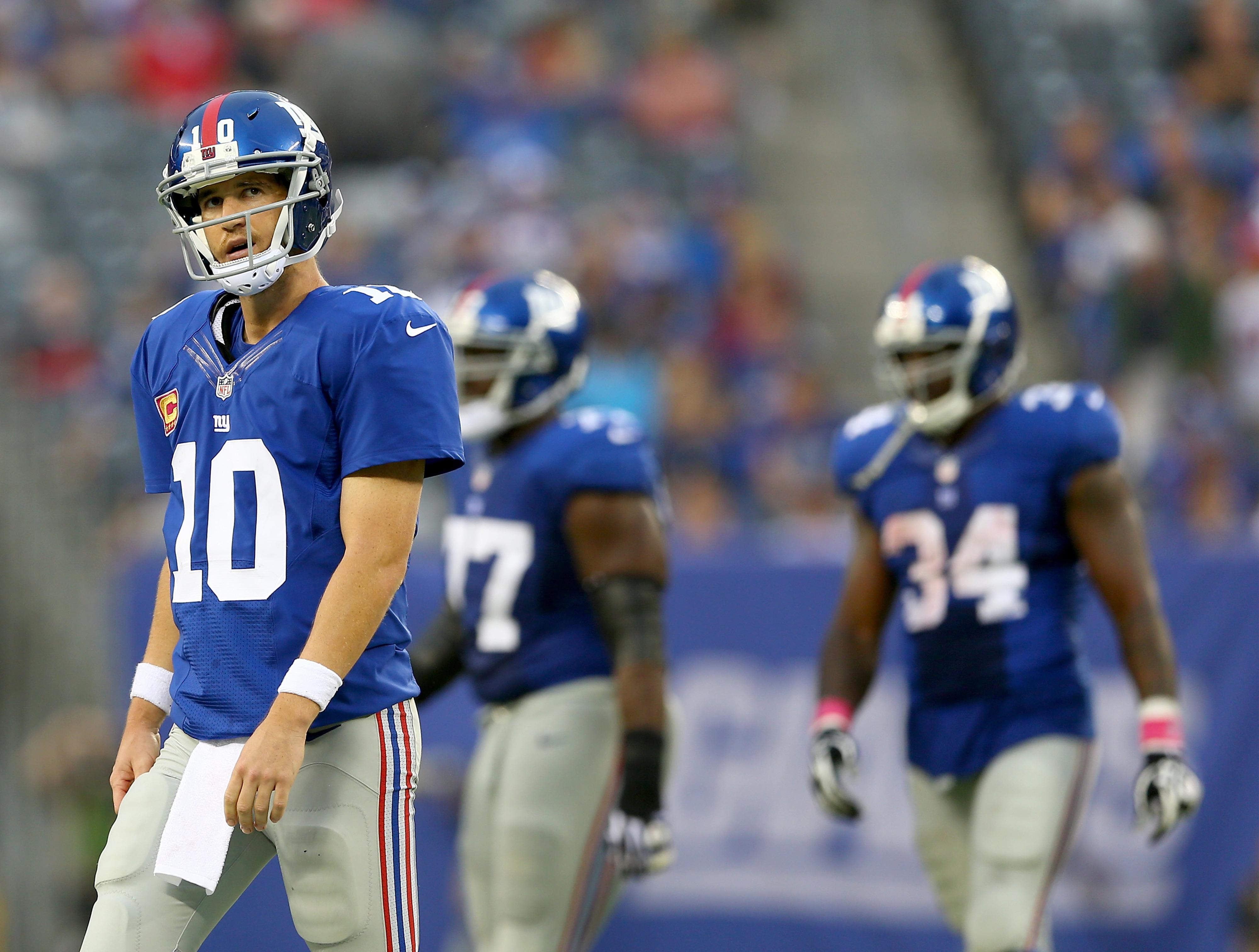 Eli Manning walks off the field after throwing one of his three fourth-quarter interceptions on Sunday.