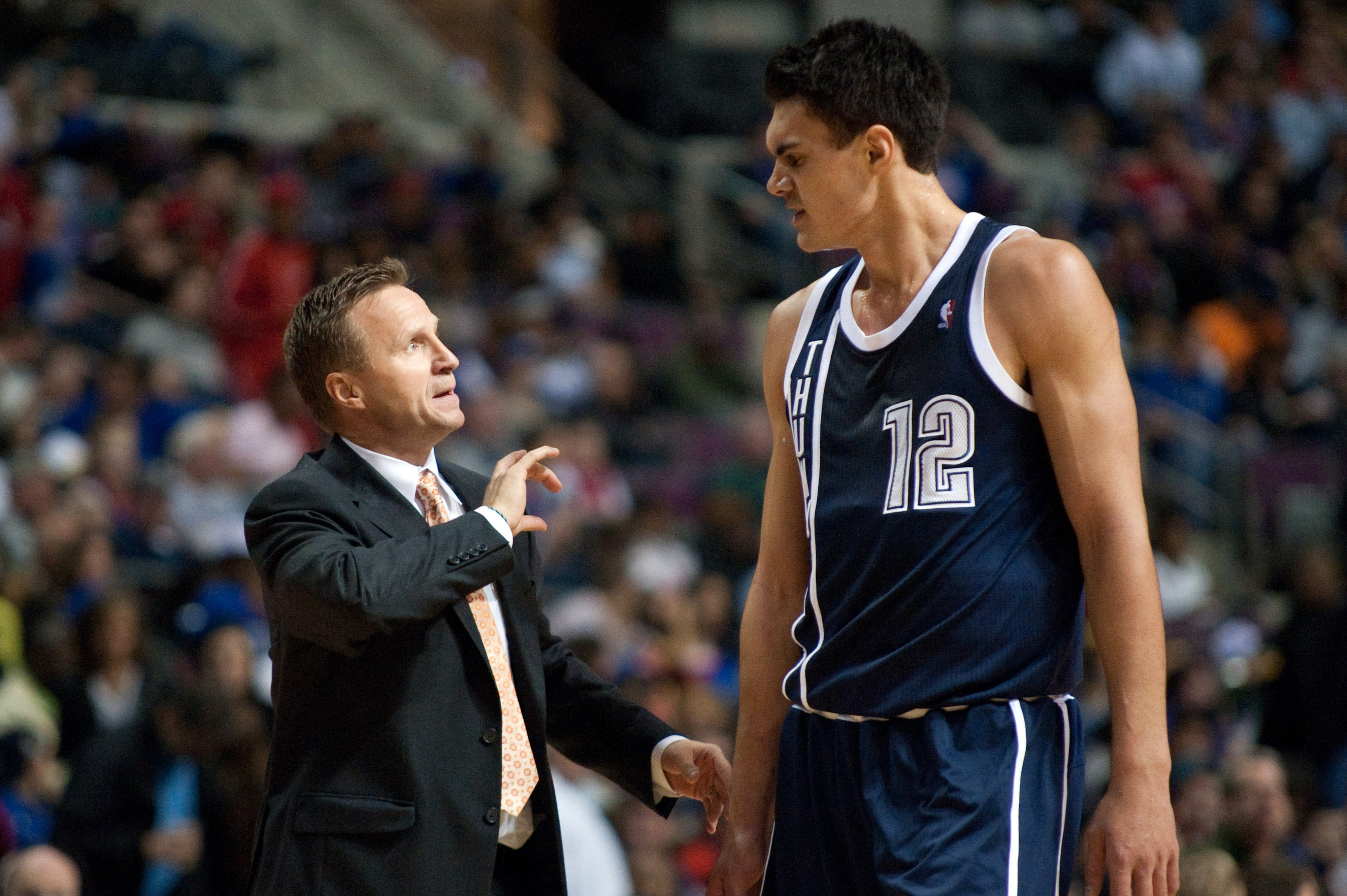 Scott Brooks is showing Steven Adams the perfect way to hold a cheeseburger.