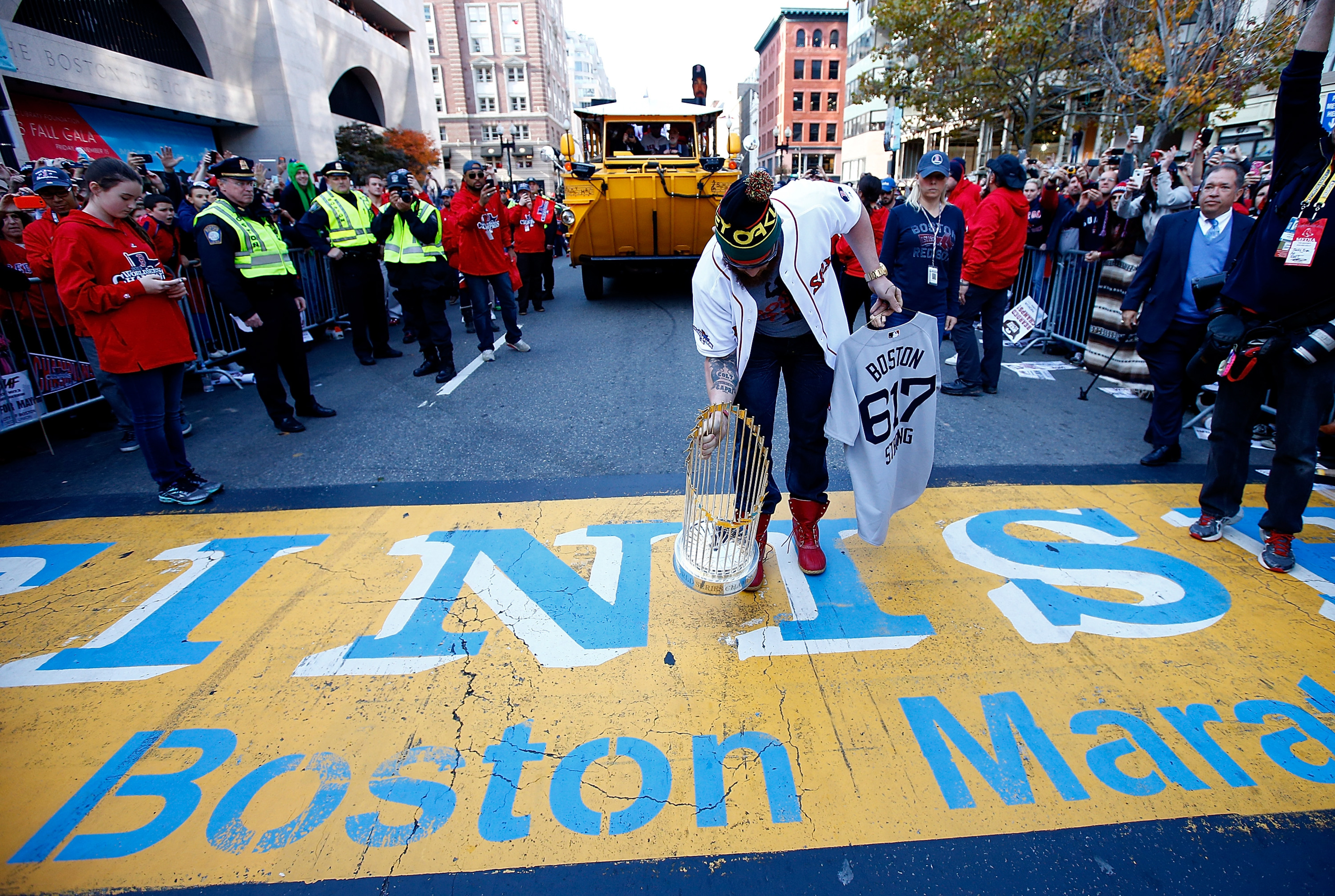Jonny Gomes of the Boston Red Sox lays the World Series trophy onto the finish line of the Boston Marathon on Boylston Street during the World Series victory parade on November 2, 2013 in Boston, Massachusetts.
