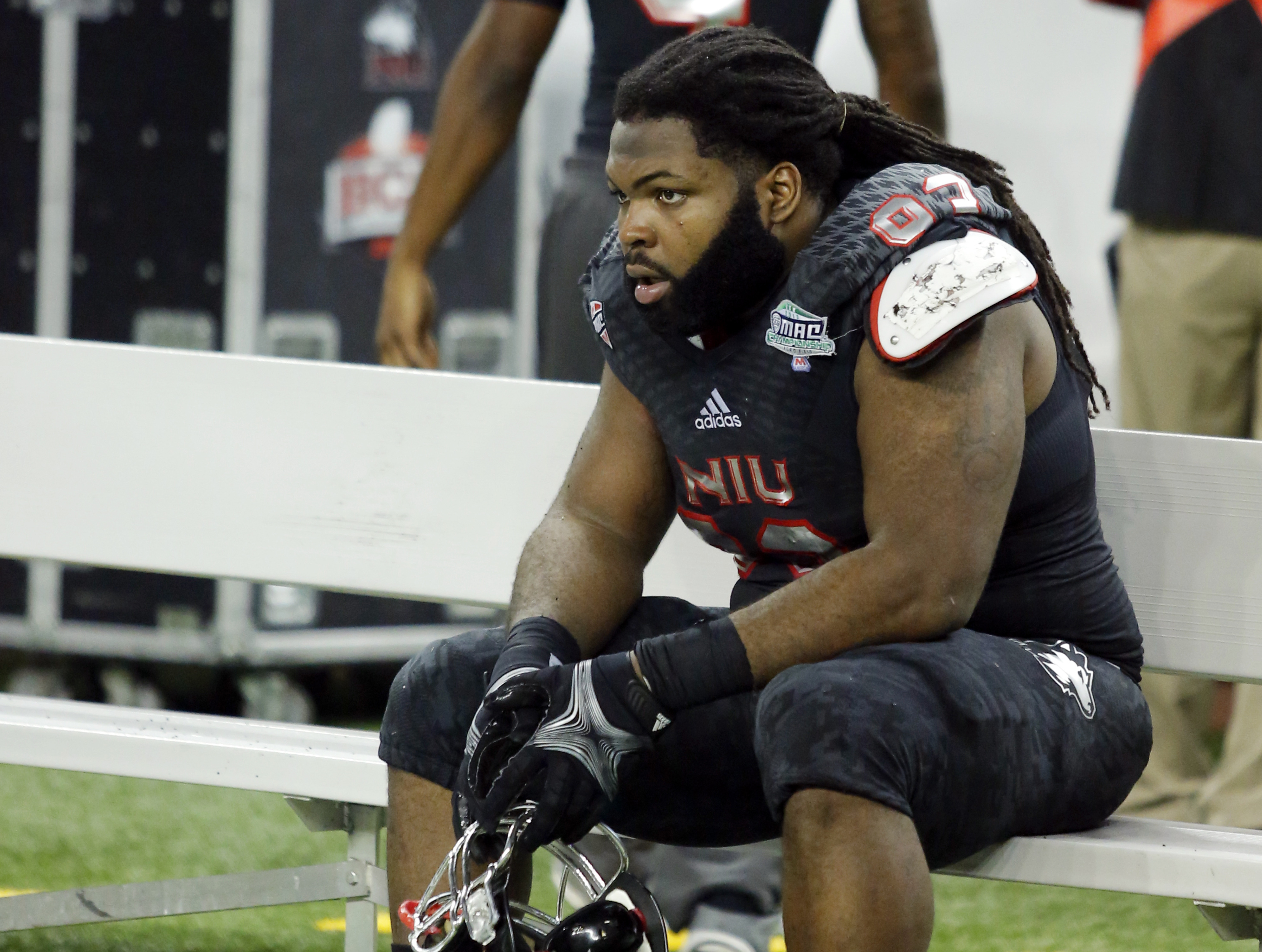 NIU defensive end Ken Bishop sits, stunned, after NIU's 47-27 loss in the MAC Championship Friday.