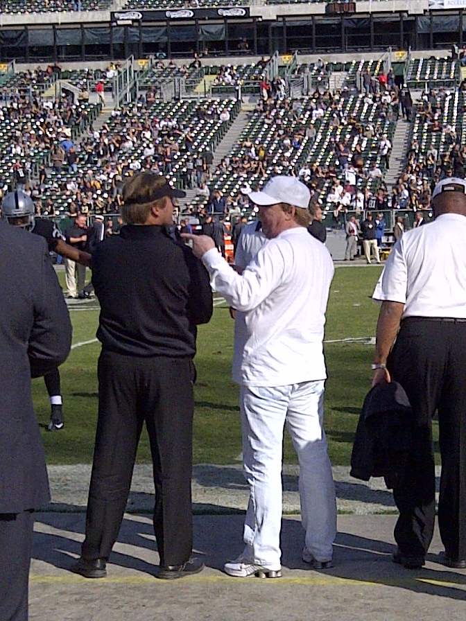 Jon Gruden and Mark Davis speak on the sidelines prior to a Monday Night game in 2012