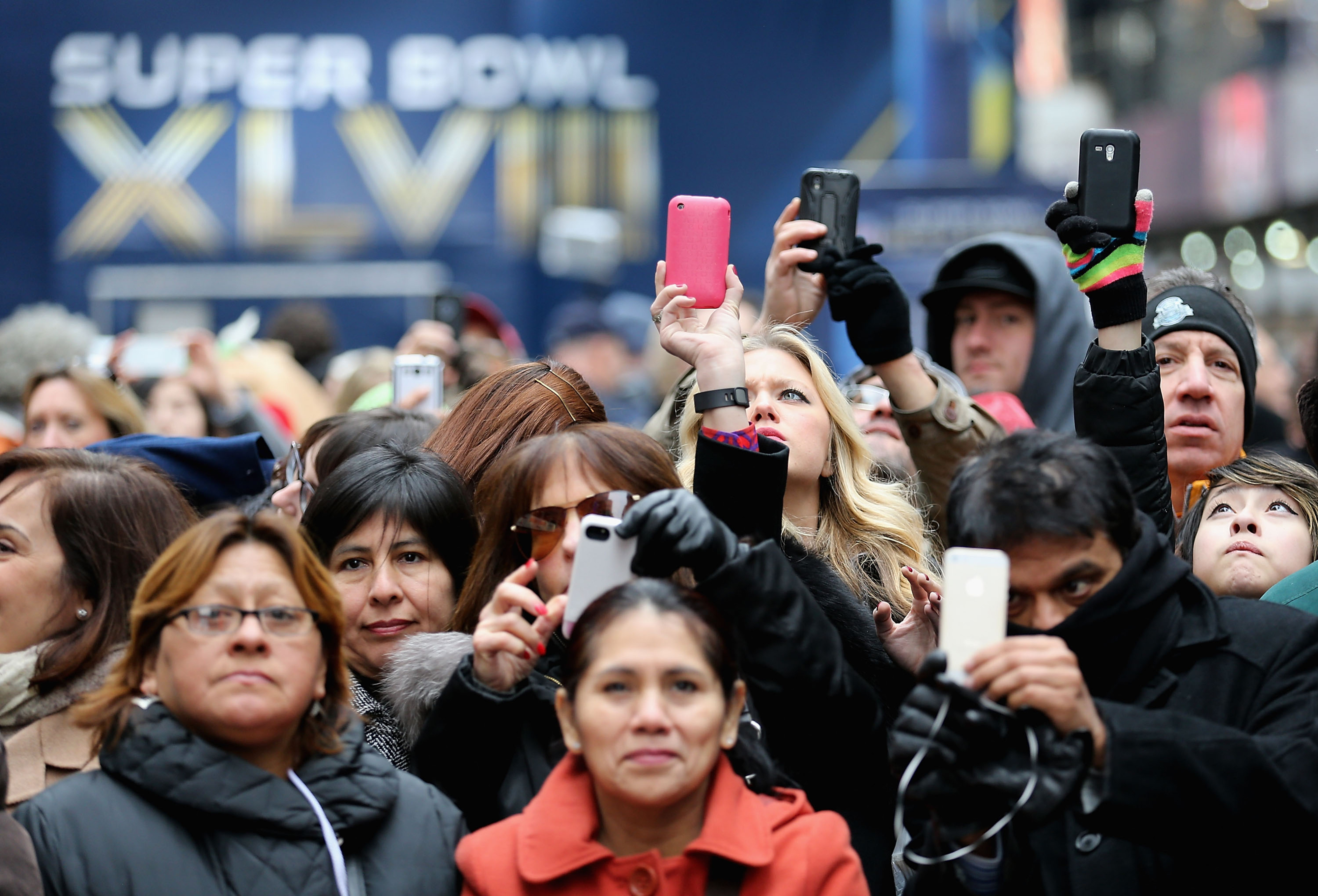 Onlookers take photos while walking through Times Square Friday