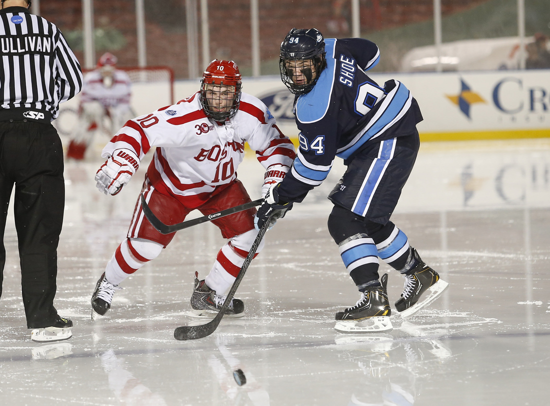 Maine forward Devin Shore (#94) battling for the puck