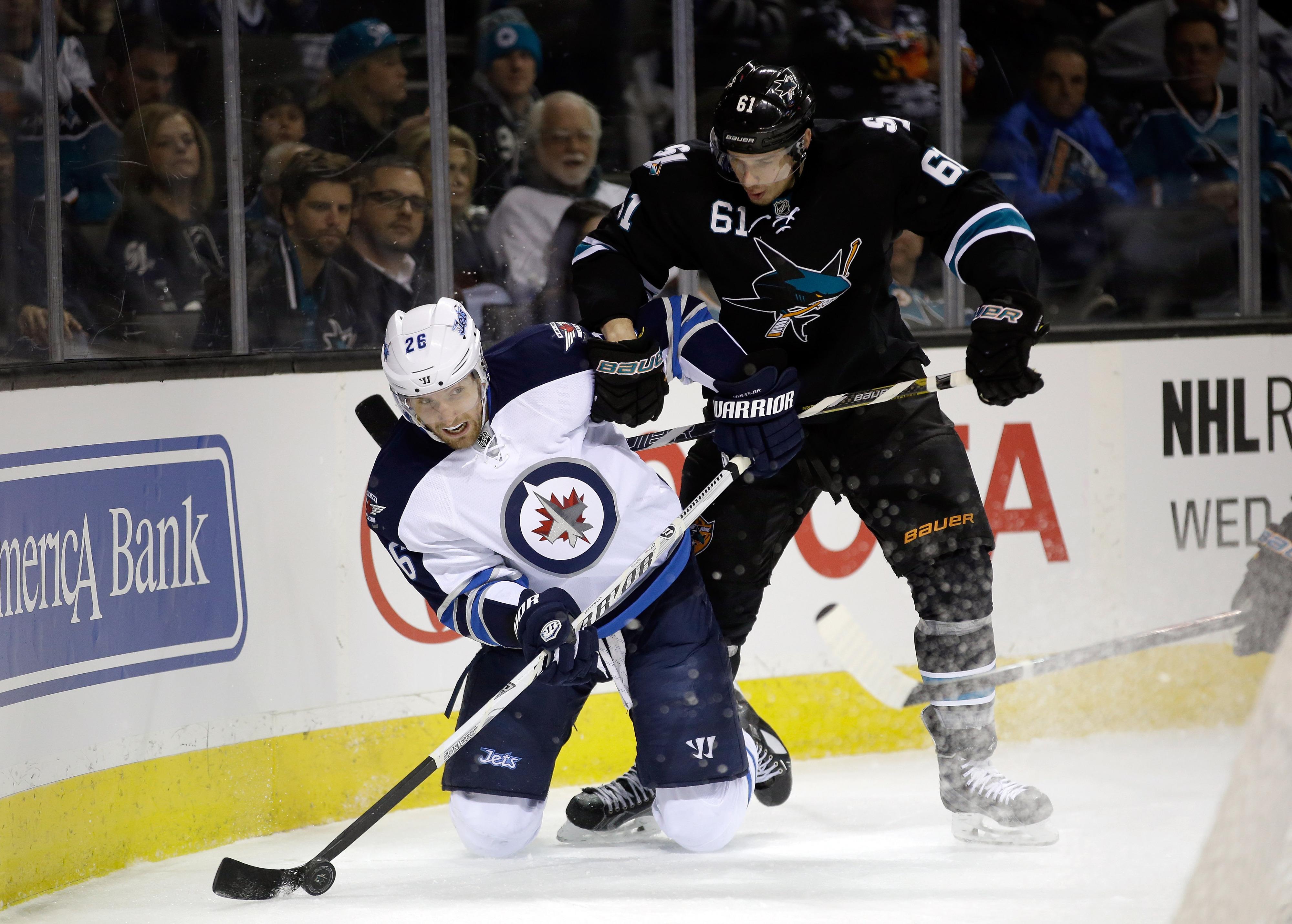 Sharks #61 Justin Braun battle Jets #26 Blake Wheeler for the puck