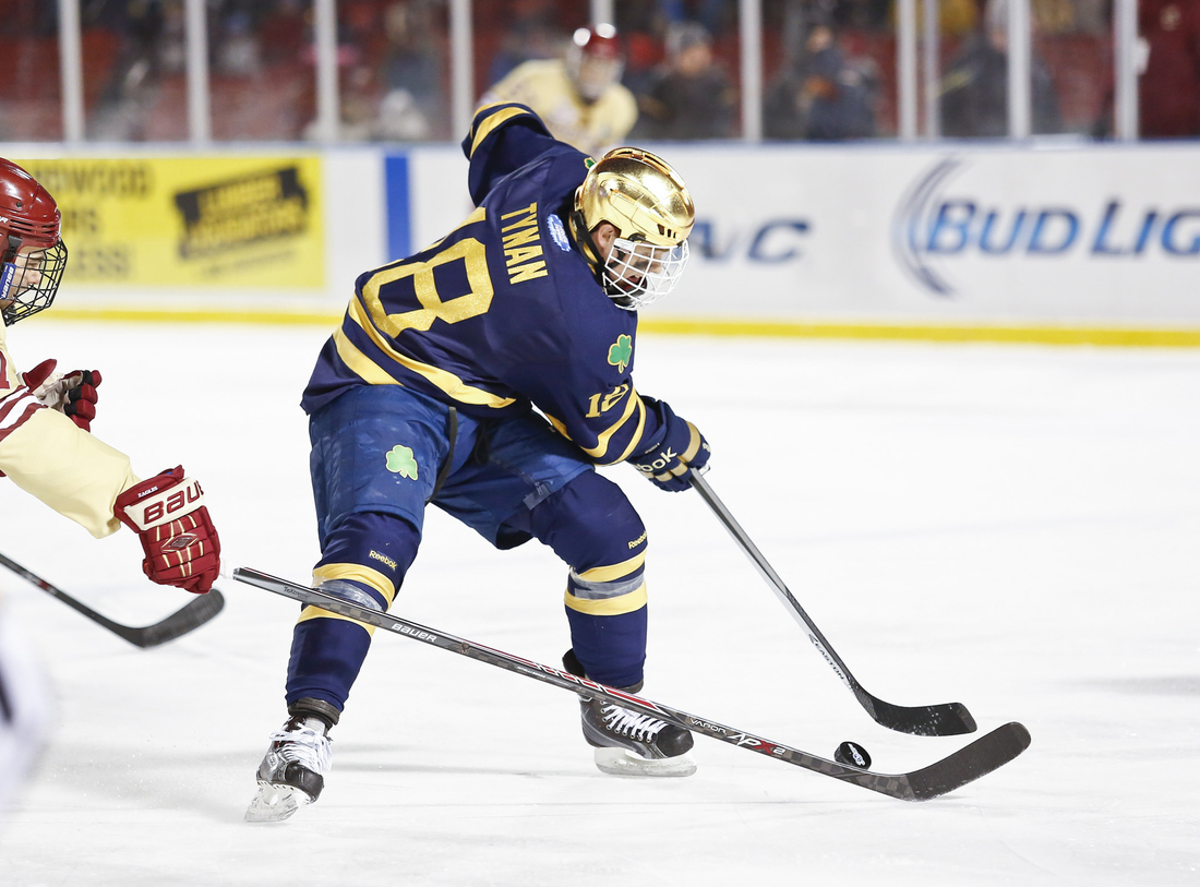 Notre Dame senior forward T.J. Tynan stick handles the puck against Boston College at Fenway Park.