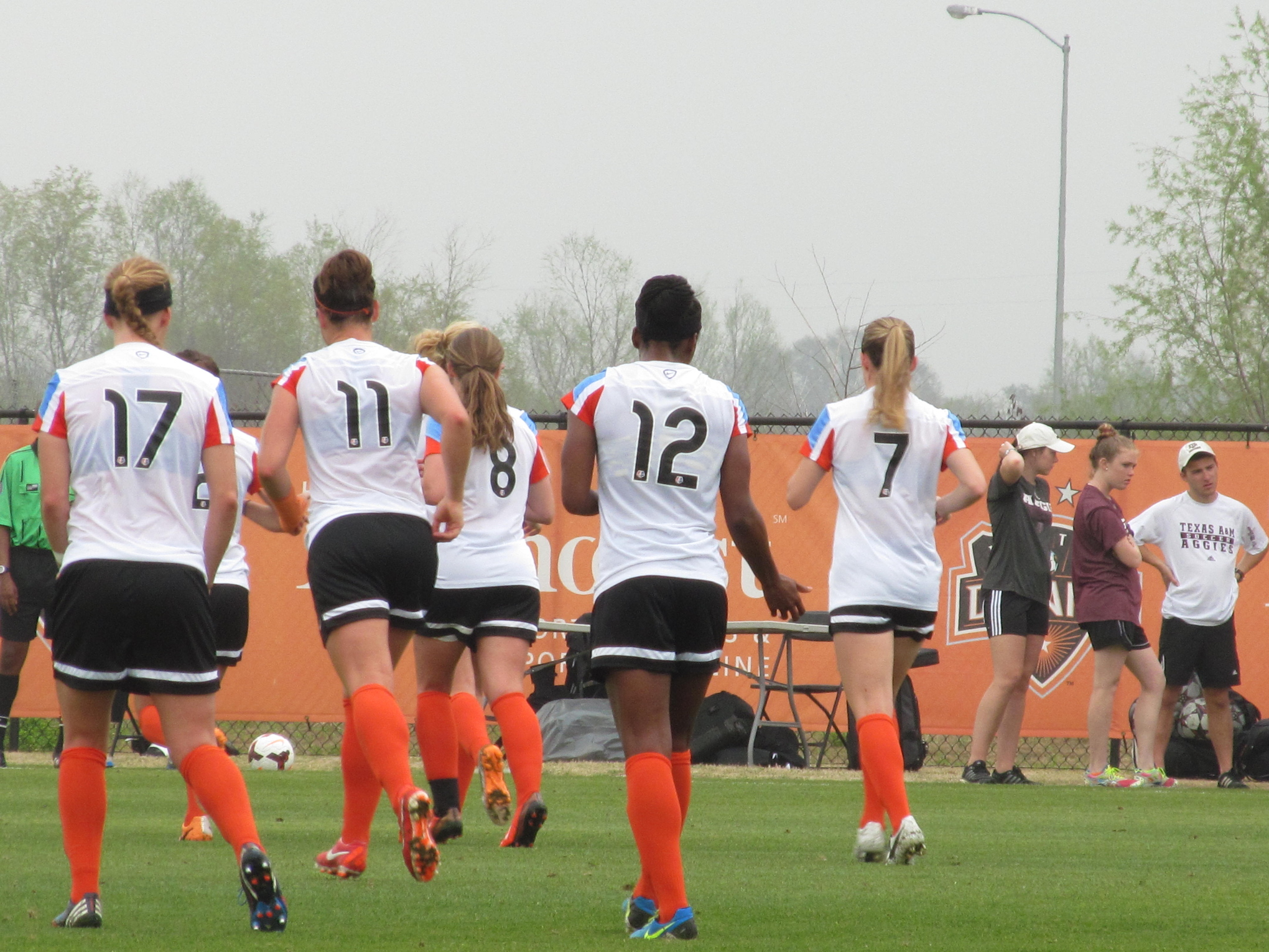 Houston Dash players walk off the pitch during a preseason match.