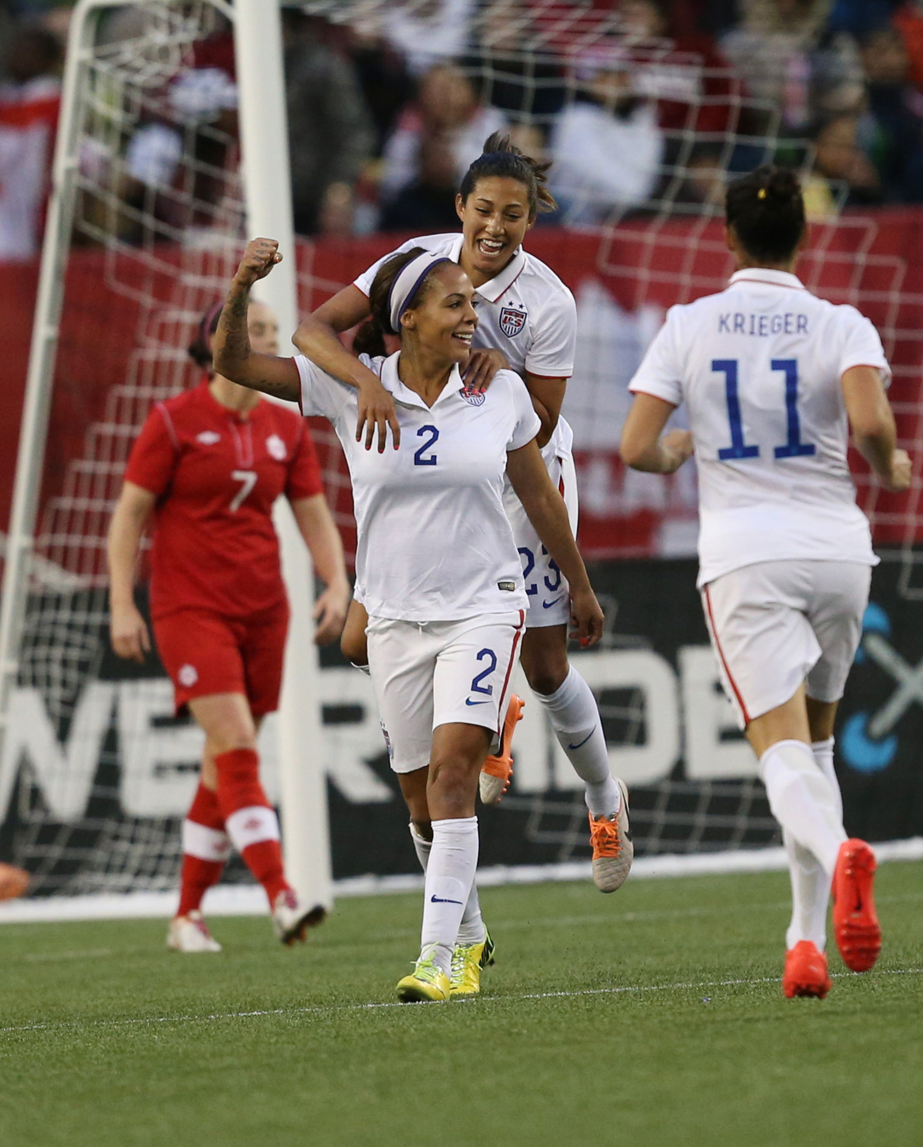 Sydney Leroux (2) celebrates her tying goal in last night's match as Carli Lloyd and Ali Krieger thank her for choosing the USA over, y'know, Canada.
