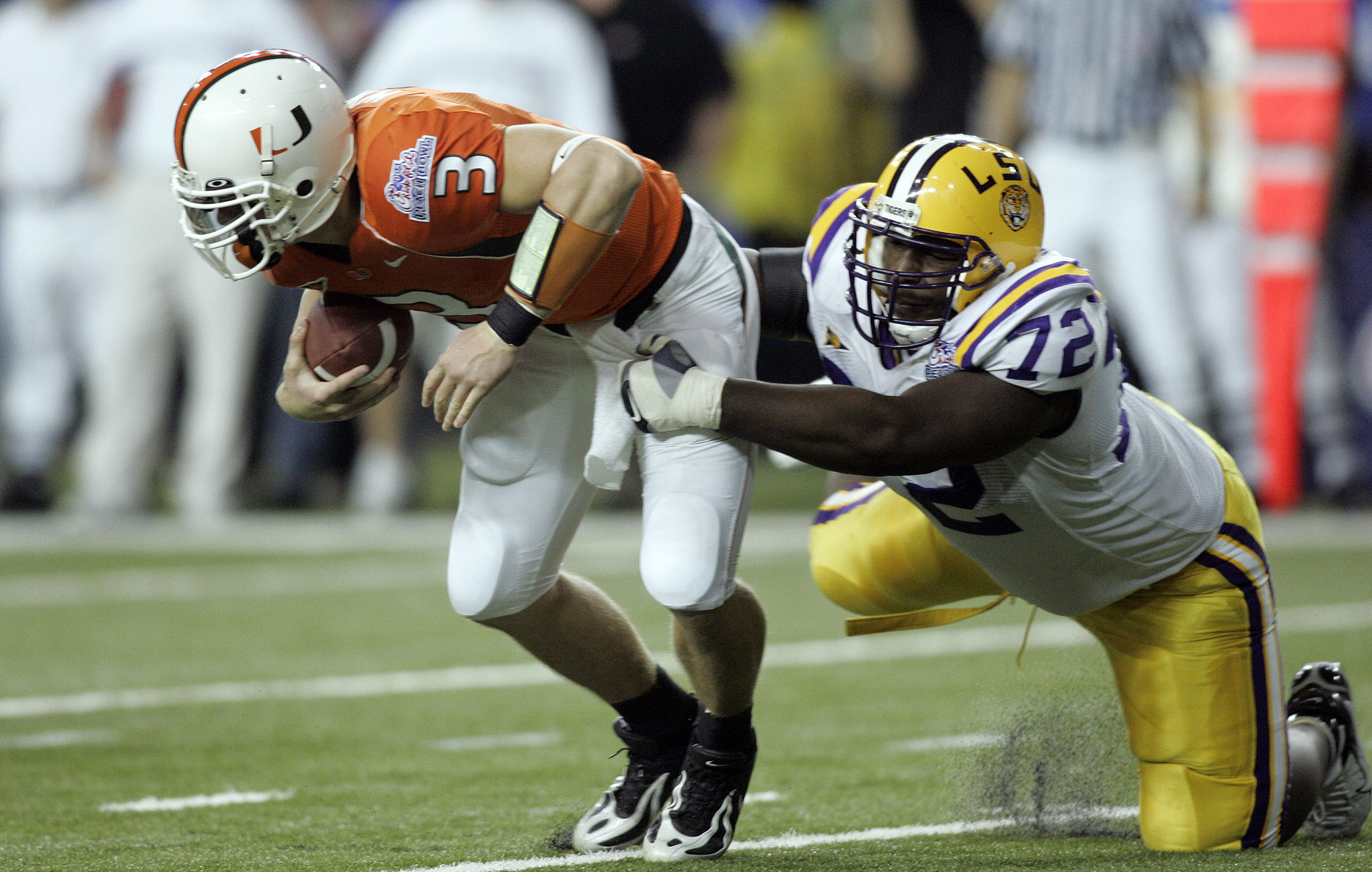 Miami's #3 Kyle Wright is sacked by Louisiana State's #72 Glenn Dorsey during the Tigers win over Miami on December 30, 2005