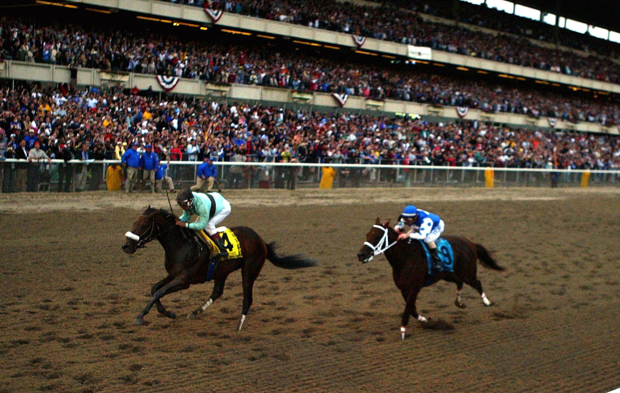 ELMONT, NEW YORK - JUNE 5: Birdstone (4), riden by Edgar Prado, overtakes Smarty Jones (9), riden by Stewart Elliott, to win the 136th Belmont Stakes on June 5, 2004 at Belmont Park in Elmont, New York. (Photo by Al Bello/Getty Images)