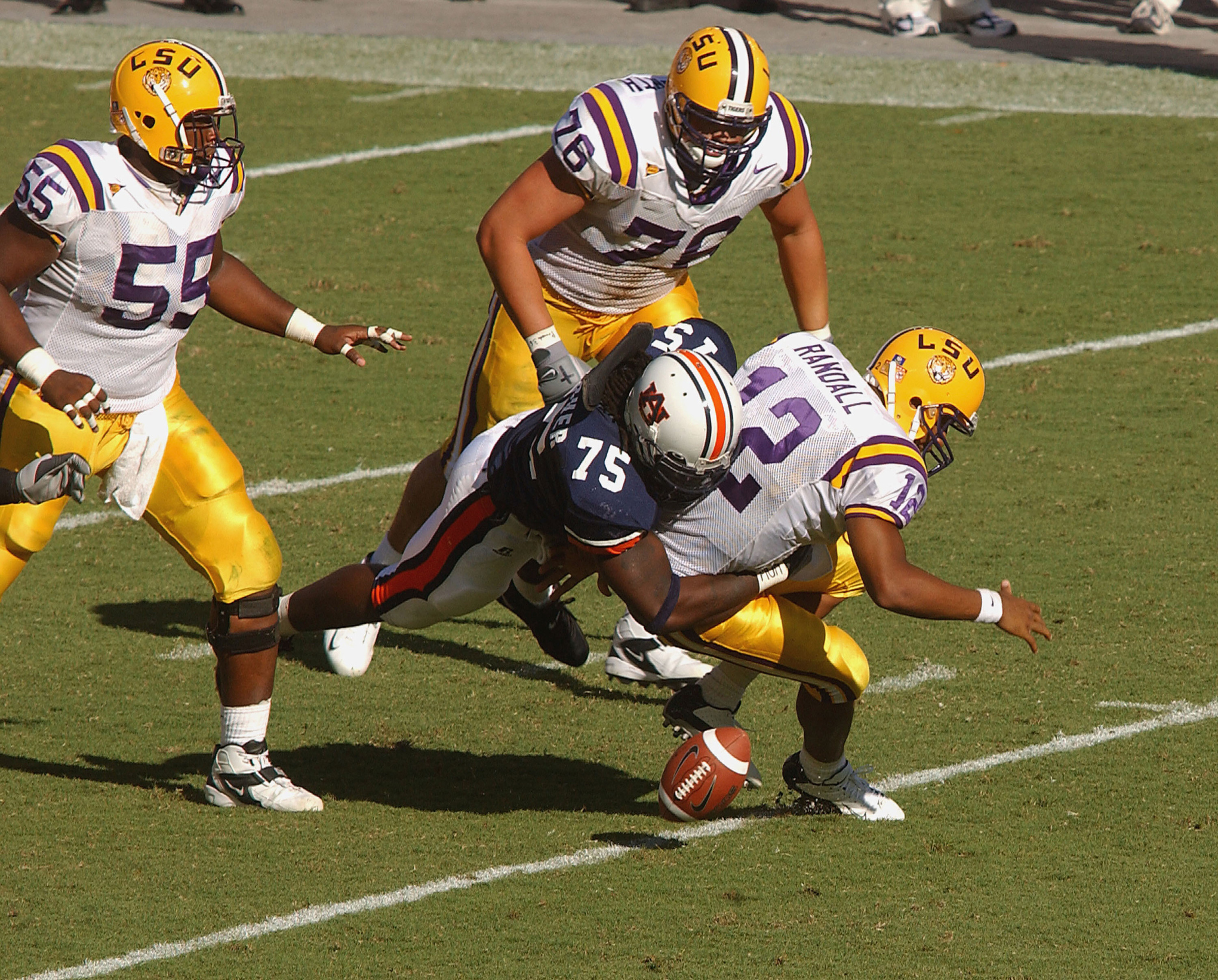 Marcus Randall #12 of the LSU Tigers fumbles after being hit by Stanley McClover #75 of the Auburn Tigers in a game on September 18, 2004 at Jordan-Hare Stadium in Auburn, Alabama.