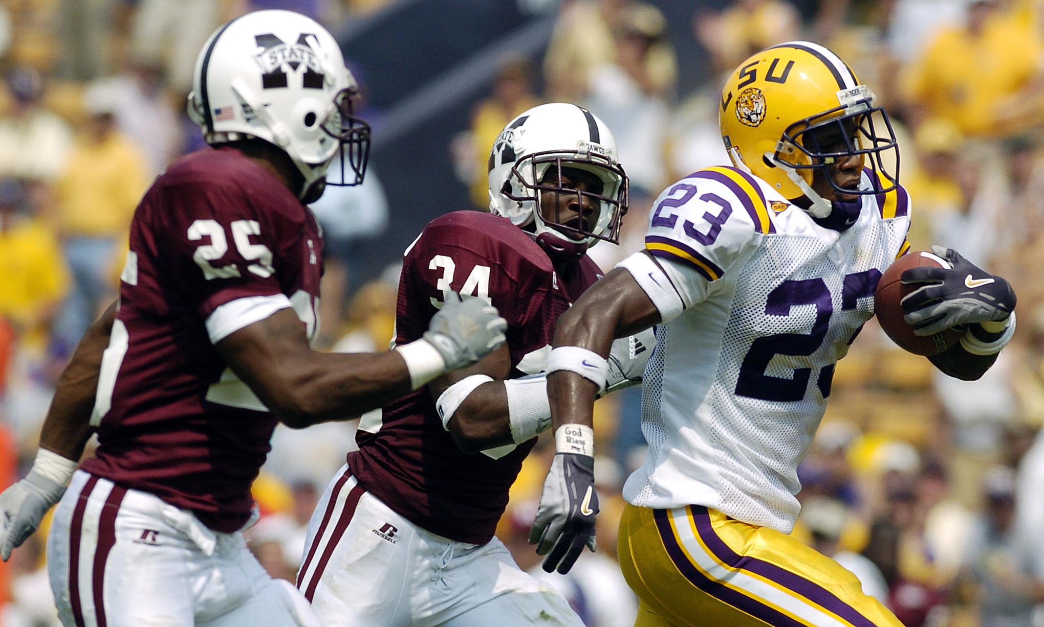 Xavier Carter #23 of Louisiana State University is chased by Slovakia Griffith #25 and Jeramie Johnson #34 of Mississippi State