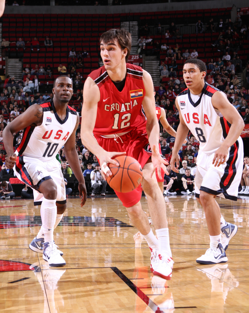 PORTLAND, OR - APRIL 7: Dario Saric #12 of the World Select Team drives against Shabazz Muhammad #10 and James Robinson #8 of the USA Junior Select Team during the 2012 Hoop Summit on April 7, 2012 at the Rose Garden Arena in Portland, Oregon.