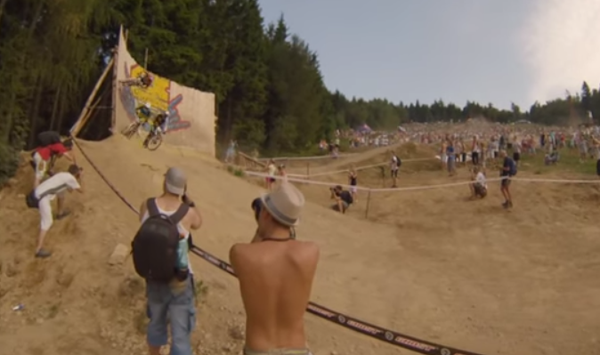 Dirt bike racer overtakes opponents with a wall ride