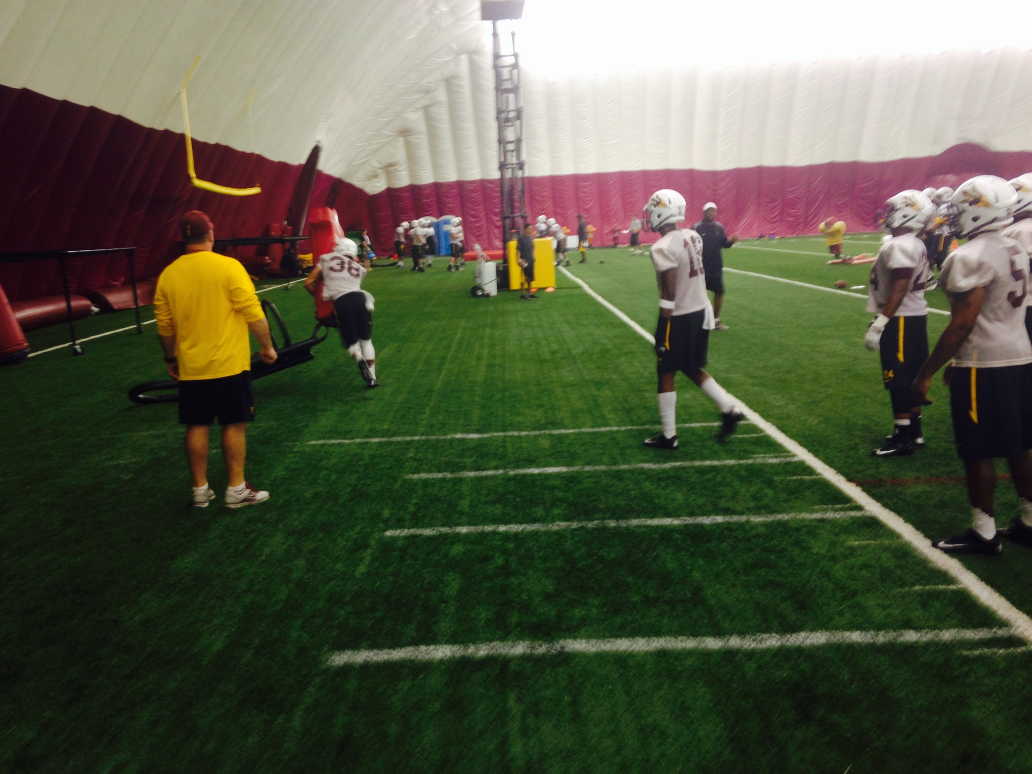 Jordan Simone hits a blocking sled as co-defensive coordinator Chris Ball looks on during practice on Aug. 7, 2014