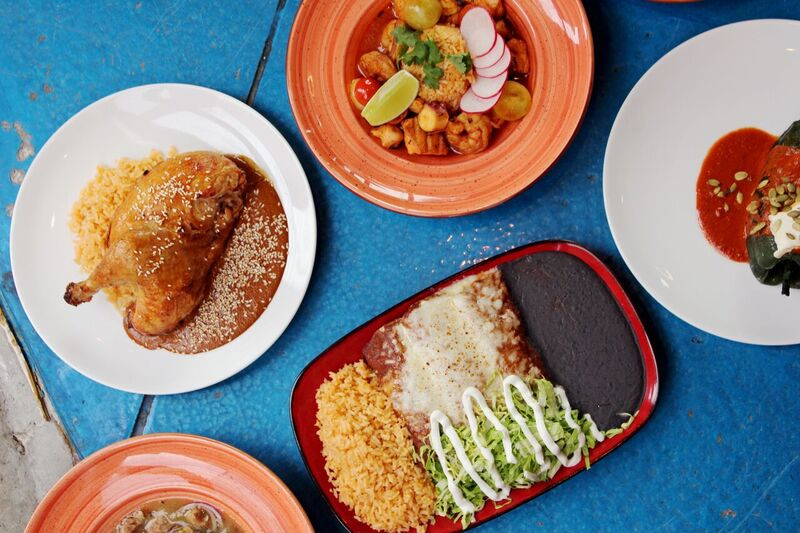 A photo from above of several Mexican dishes on plates at Que Bueno Suerte