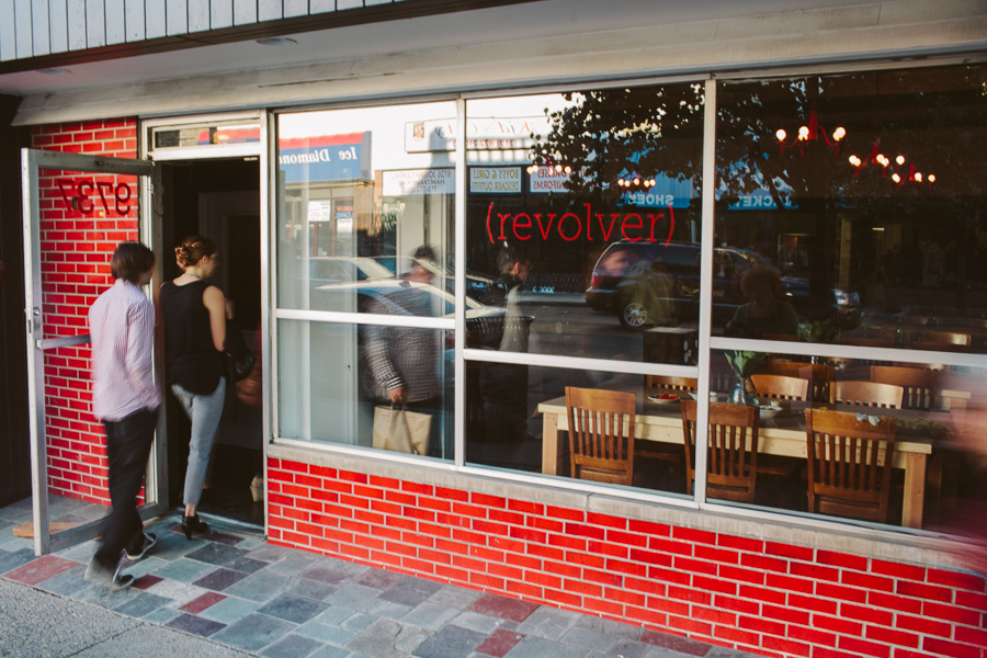 Two customers walk through the doors of Revolver's red-tiled storefront.