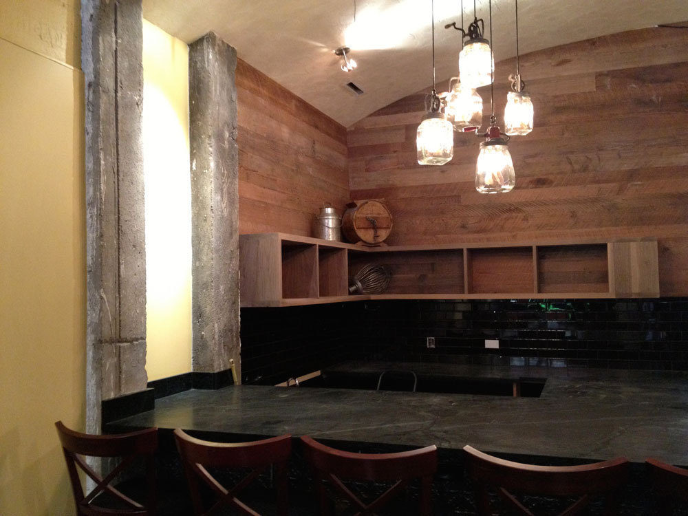 The soapstone-topped cheese and charcuterie bar with butter-churn chandelier