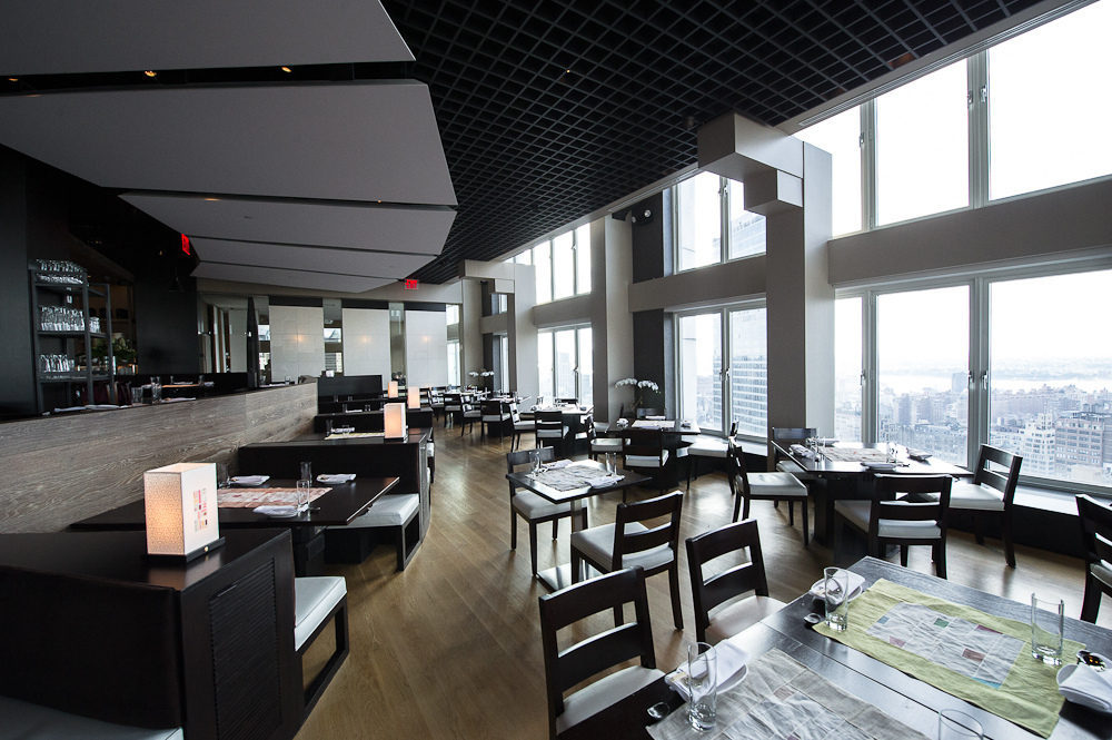 A spacious dining room is well-lit by natural light, with help from floor-to-ceiling windows that offer sweeping views of the city