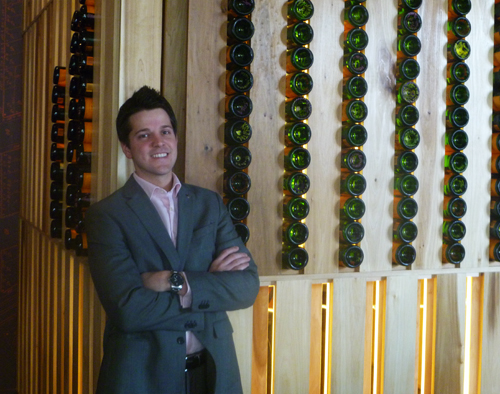 """New GM at Ste. Marie, Miles Tully, Jr., in front of the restaurant's """"champagne tower."""""""