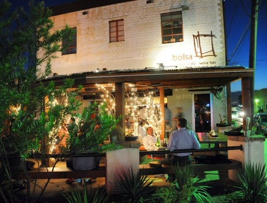 a plant-covered patio light by lights at dusk