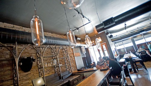 The main bar with gothic shelves and Edison bulbs