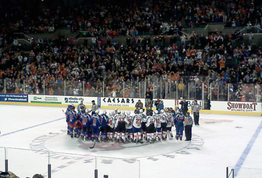 Team New York and Team Philadelphia congregate at center ice for a group photo after their charity game.