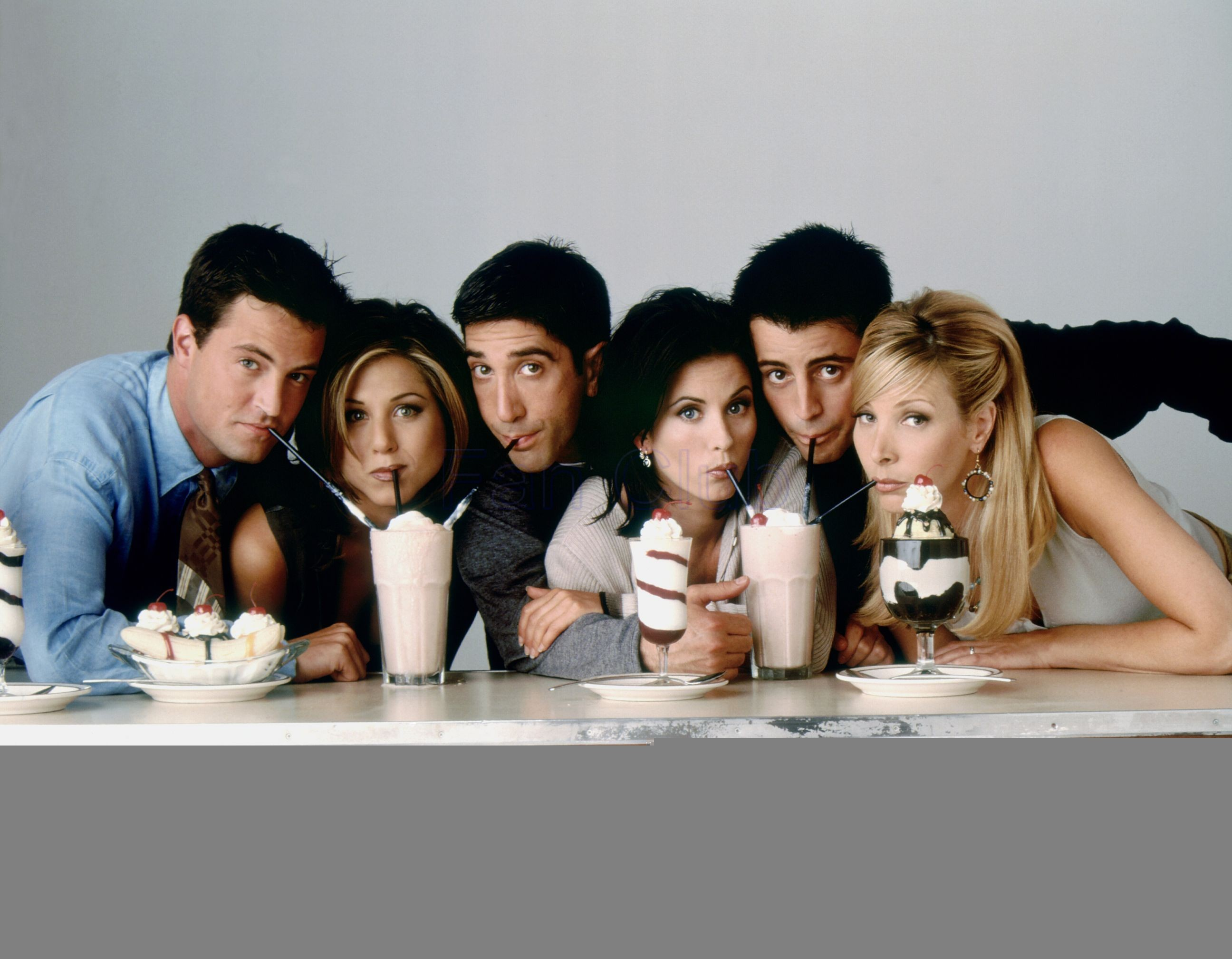 "The cast of ""Friends"" leaning forward and sipping on milkshakes sitting on a table."