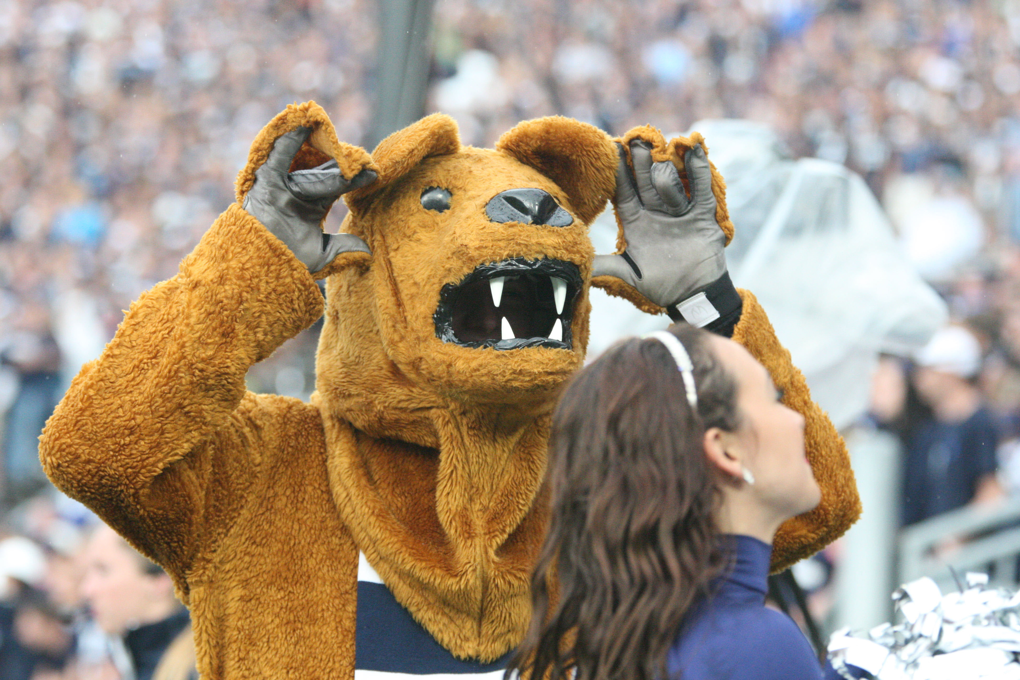 That poor, unsuspecting cheerleader is about to be eaten by the Nittany Lion.