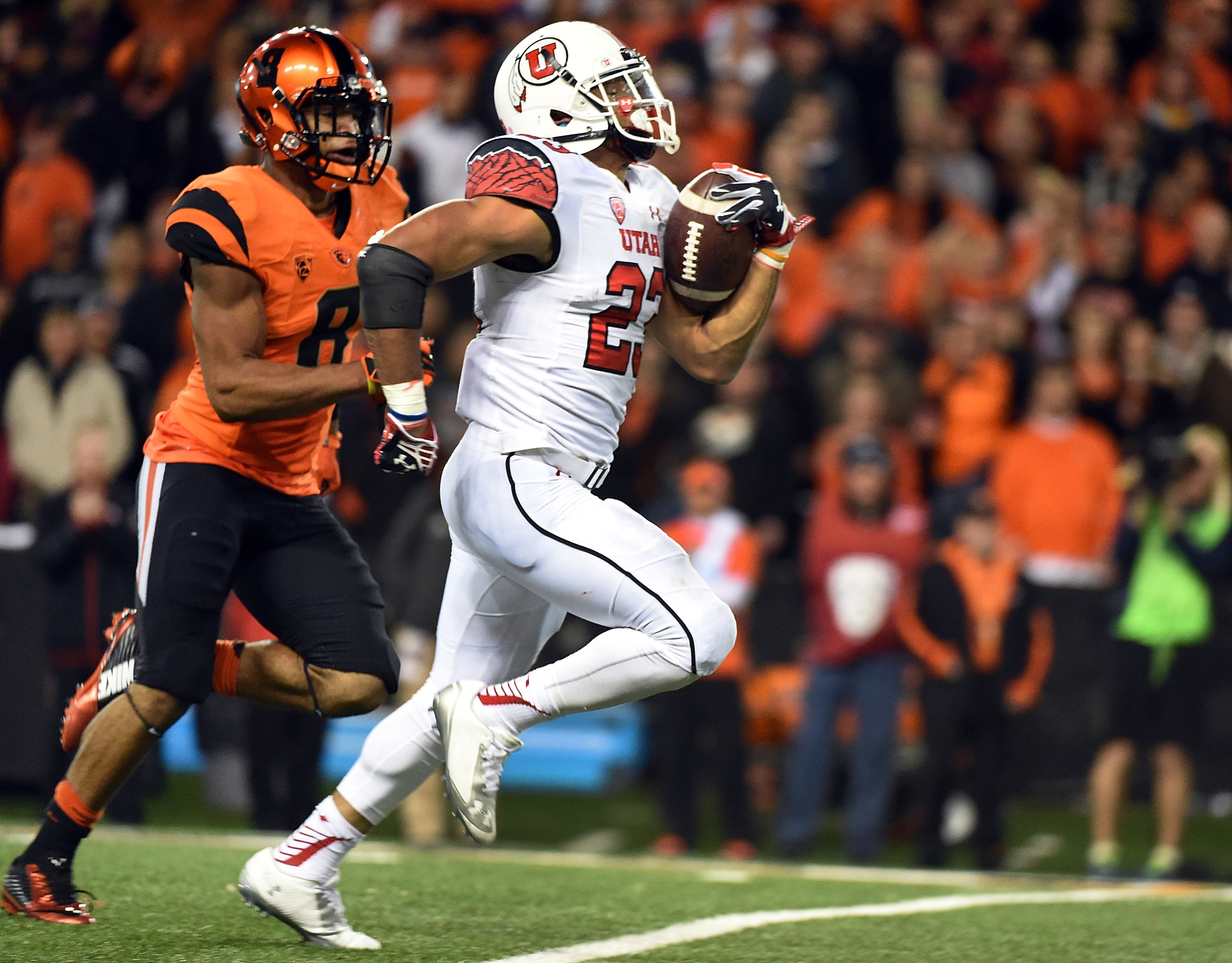 Utah running back Devontae Booker (23) scored the go-ahead touchdown in regulation, and a touchdown in each of the overtimes to will Utah to the victory over Oregon State in Corvallis, Ore.