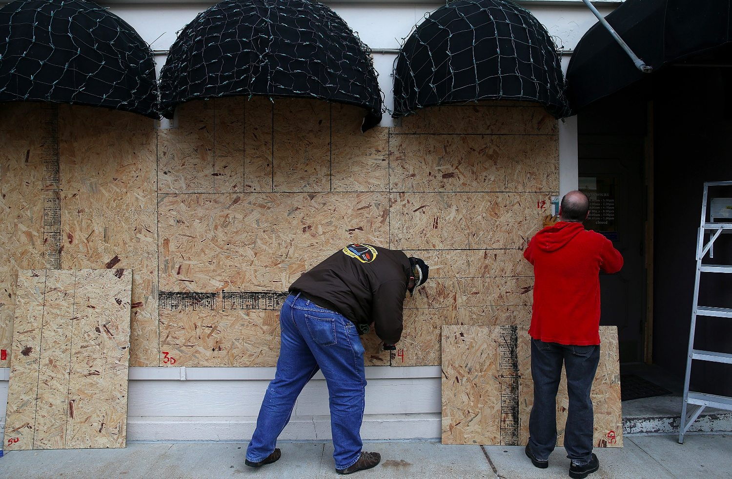 Workers board up windows at a restaurant near the Buzz Westfall Justice Center.