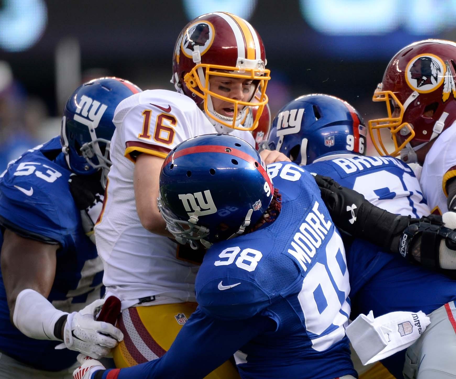 Washington quarterback Colt McCoy is sandwiched by Giants defenders