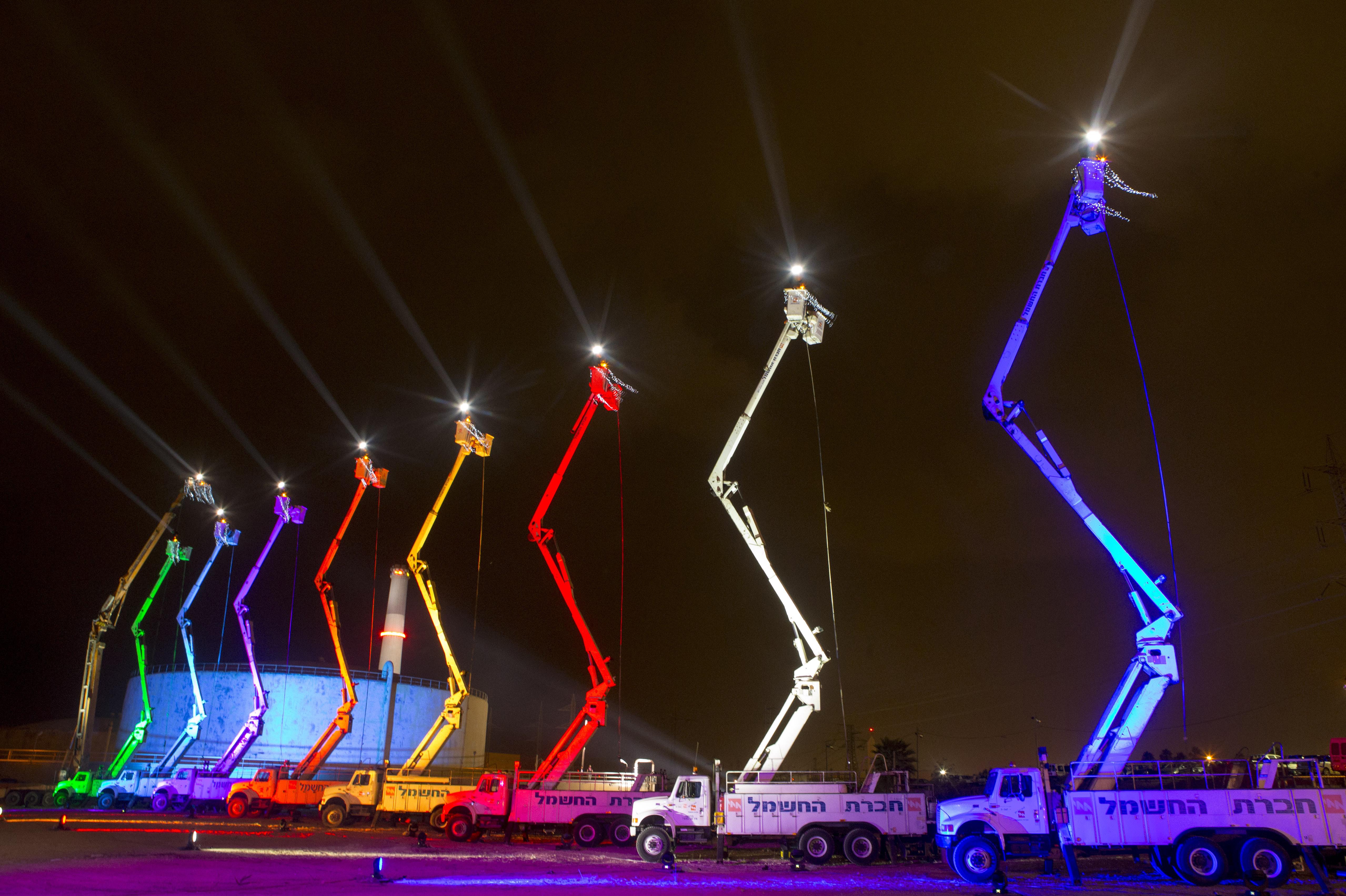An Israeli electric  company arranges cranes in the shape of a Hanukkah menorah.