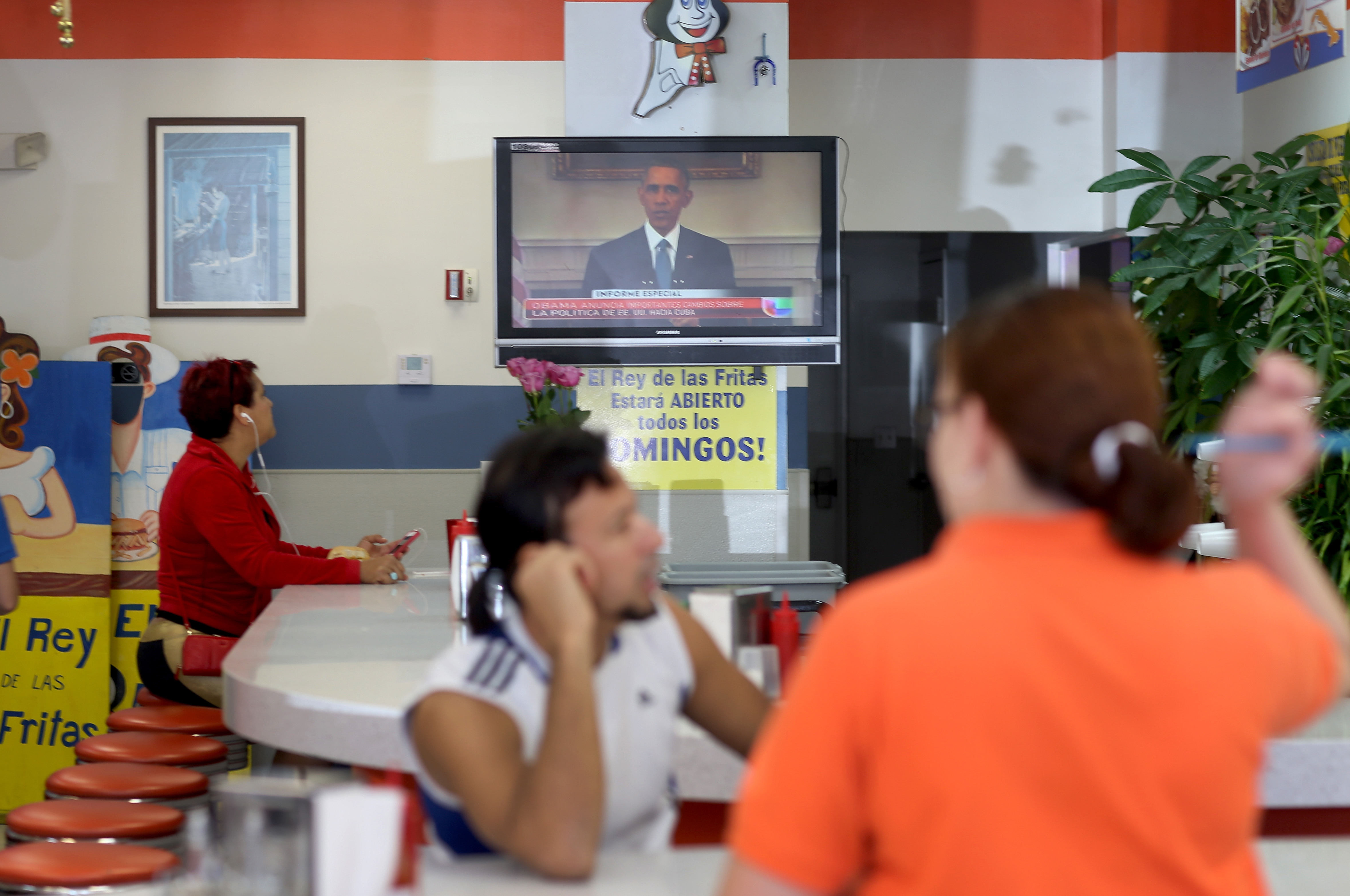 People watch Obama's Cuba announcement at a cafe in Little Havana.