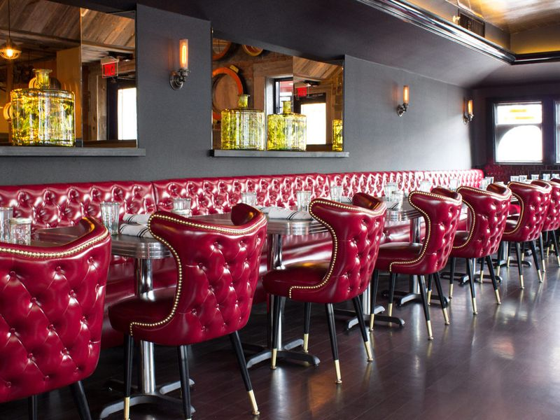 Interior of a restaurant, featuring shiny red leather chairs and banquettes, a dark gray wall, and mirrors.