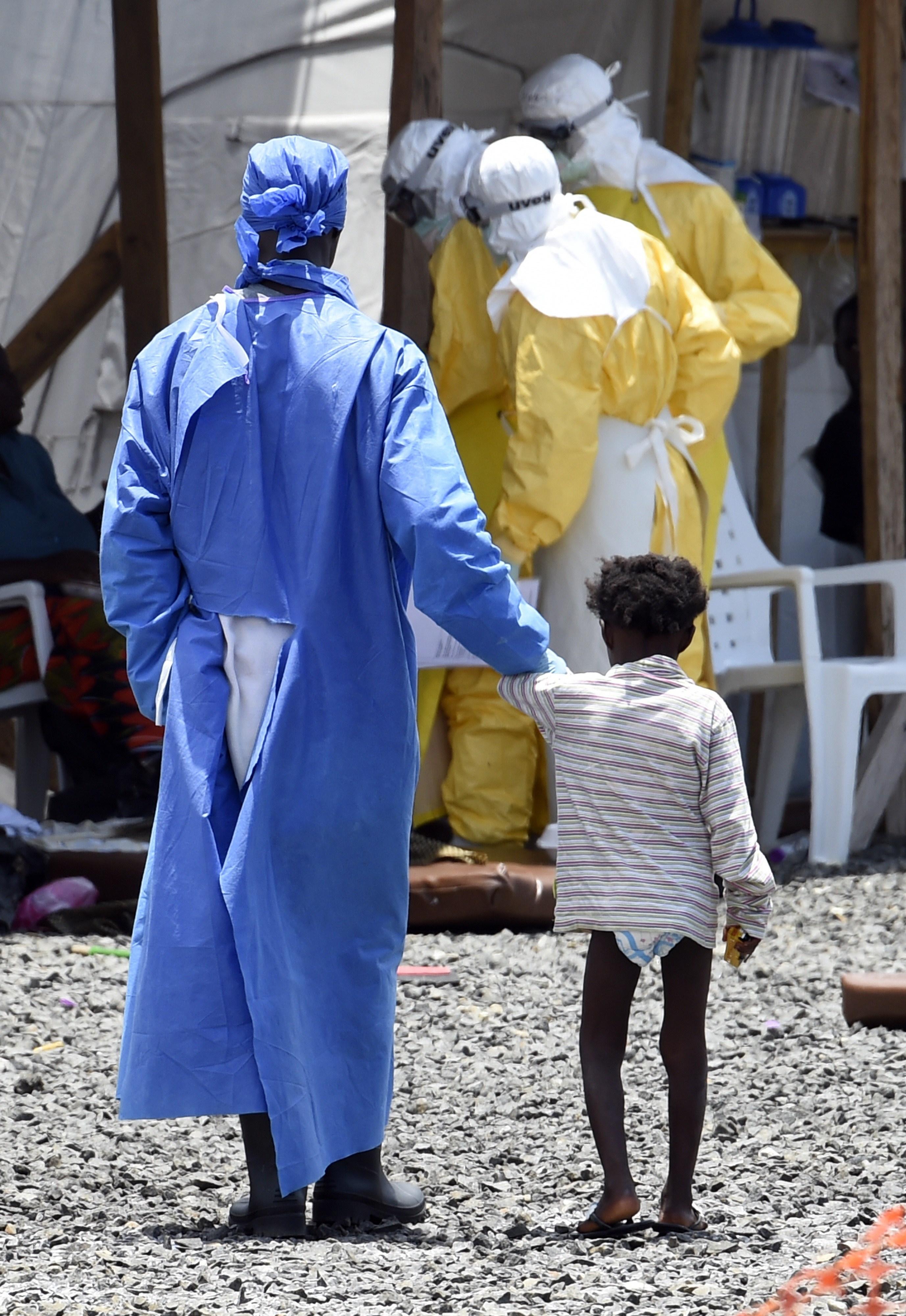 A nurse with a little girl suffering from Ebola. Monrovia, Liberia September 2014.
