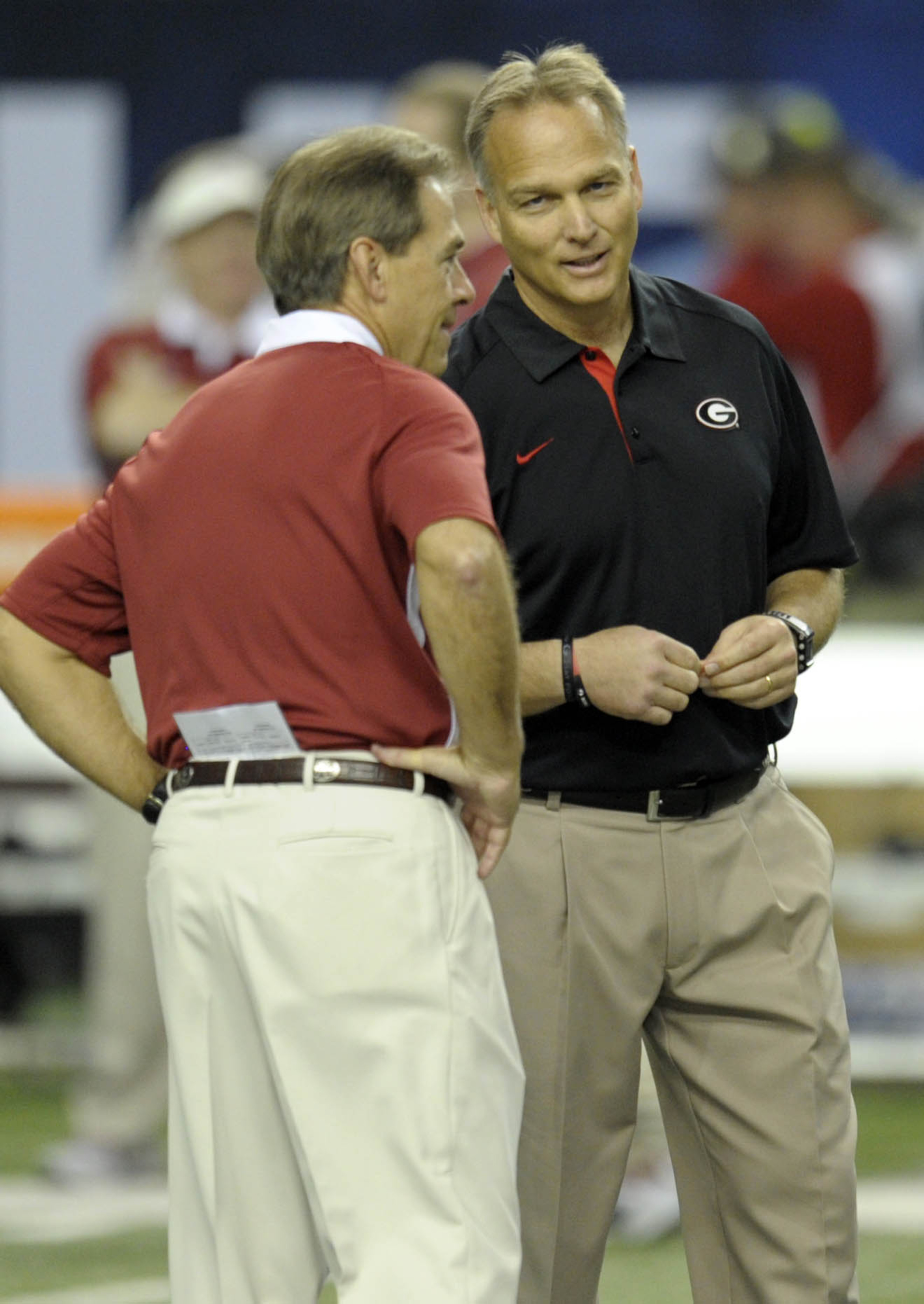 The architect of the most invincible dynastic juggernaut in college football history (left) spoke to the mediocre beneficiary of a weak schedule who lacks killer instinct (right) before their 11-1 teams played a game decided on the final snap.