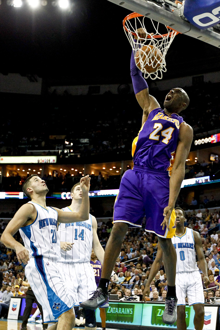 Dec 5, 2012; New Orleans, LA, USA; Los Angeles Lakers shooting guard Kobe Bryant (24) dunks over New Orleans Hornets point guard Greivis Vasquez (21) and power forward Jason Smith (14) and small forward Al-Farouq Aminu (0) during the second quarter o