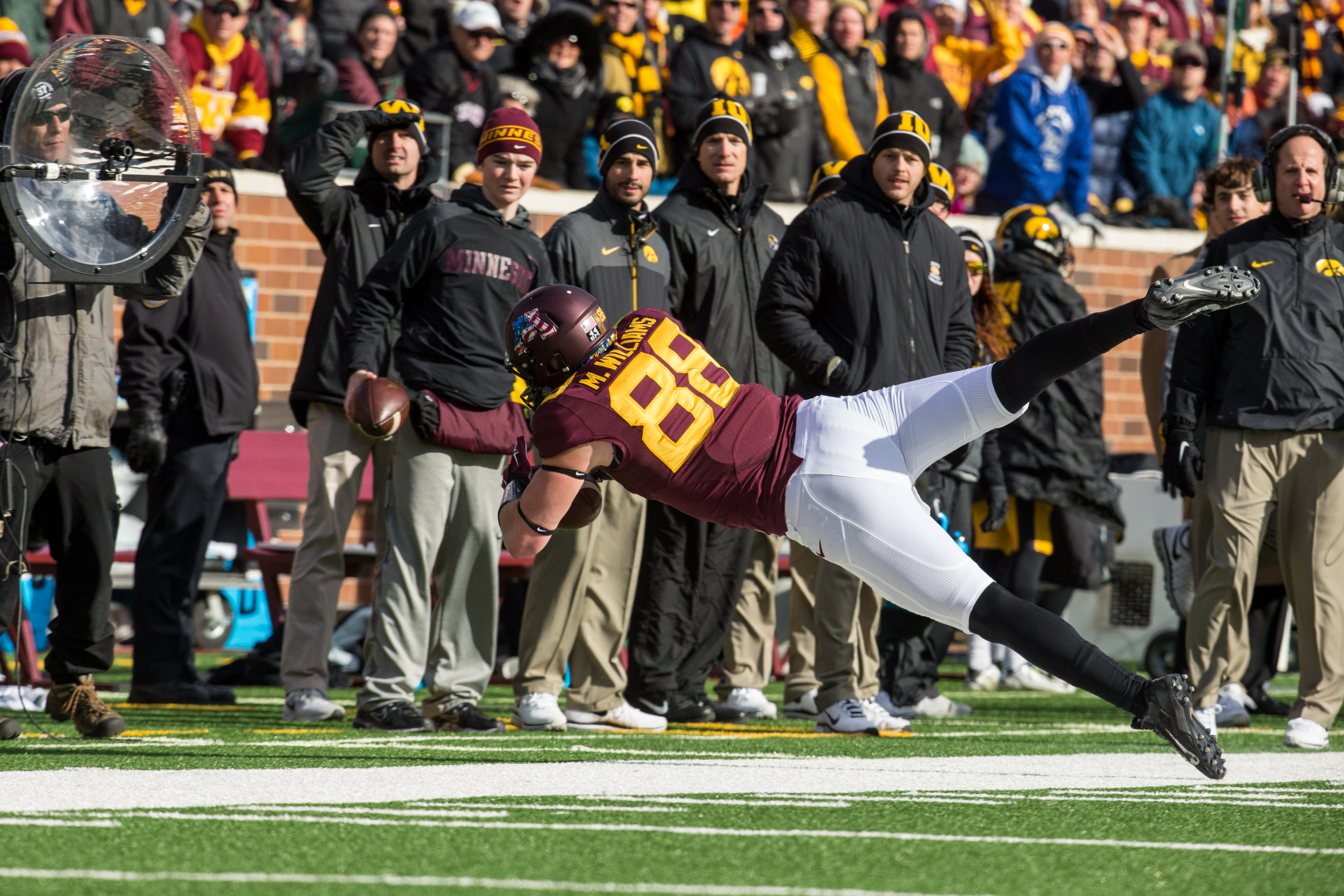 """Casey O'Brien (wearing Minnesota gear on the Iowa sideline) during Maxx Williams famous """"rubber wake"""" catch."""