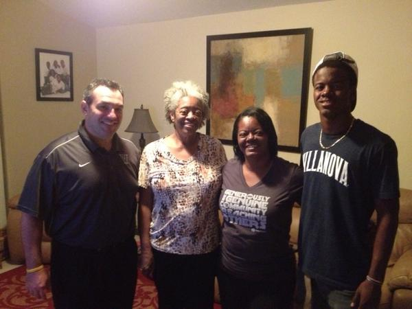 Trey Johnson (right) poses with his family and Villanova coach Roc Bellantoni (left) upon his official commitment to  the Wildcats.