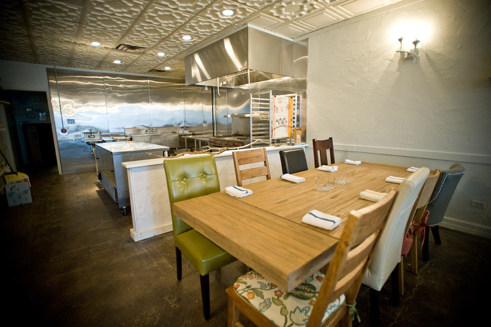 A wooden table with different styles of high backed chairs and a stainless steel open kitchen.