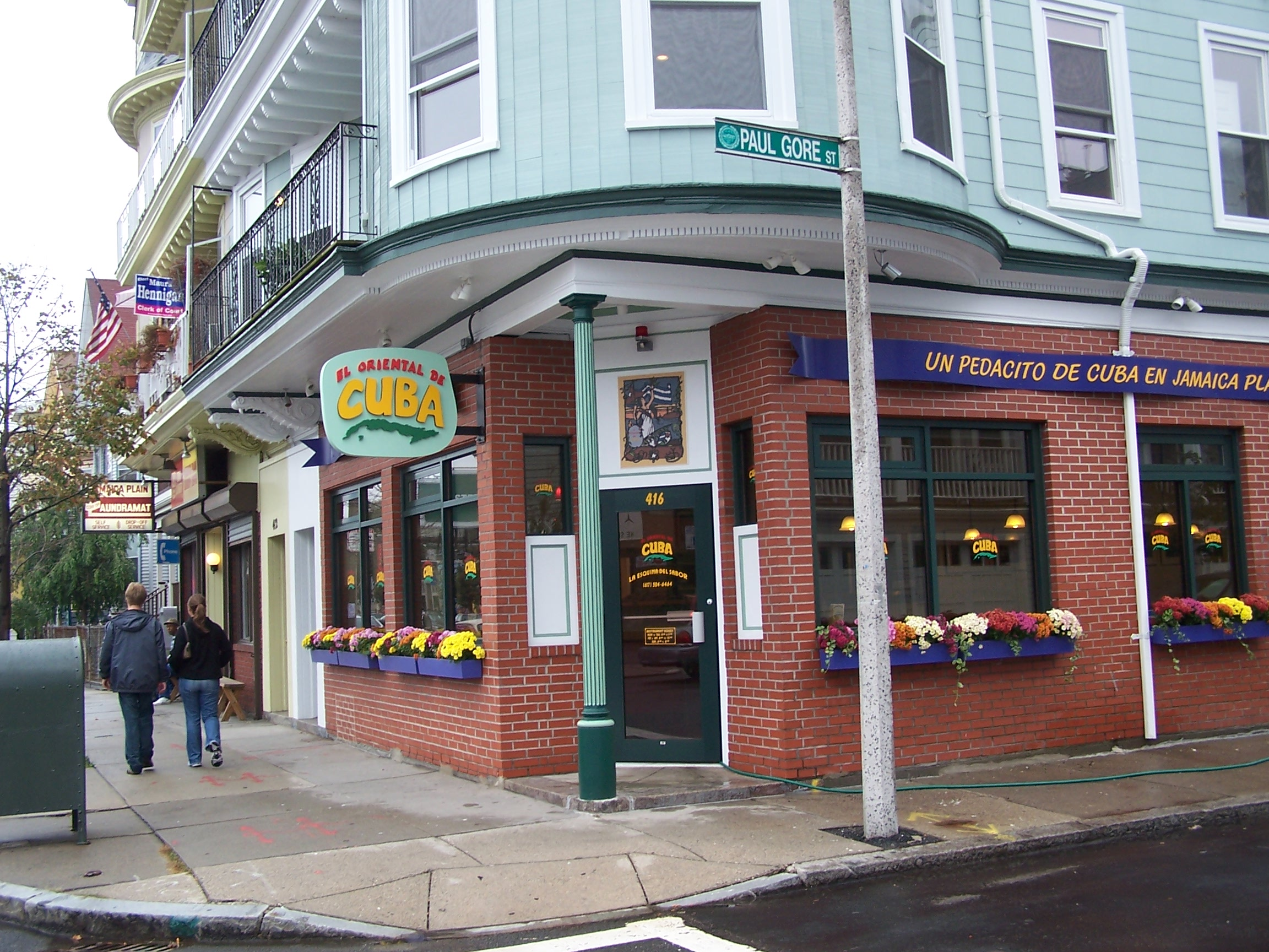 Exterior shot of a casual corner restaurant with brick walls, large windows decorated with flower boxes, and mint green signage with bright red and yellow lettering