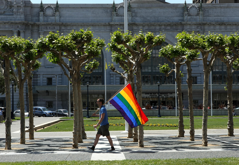 A man carries an LGBT flag.