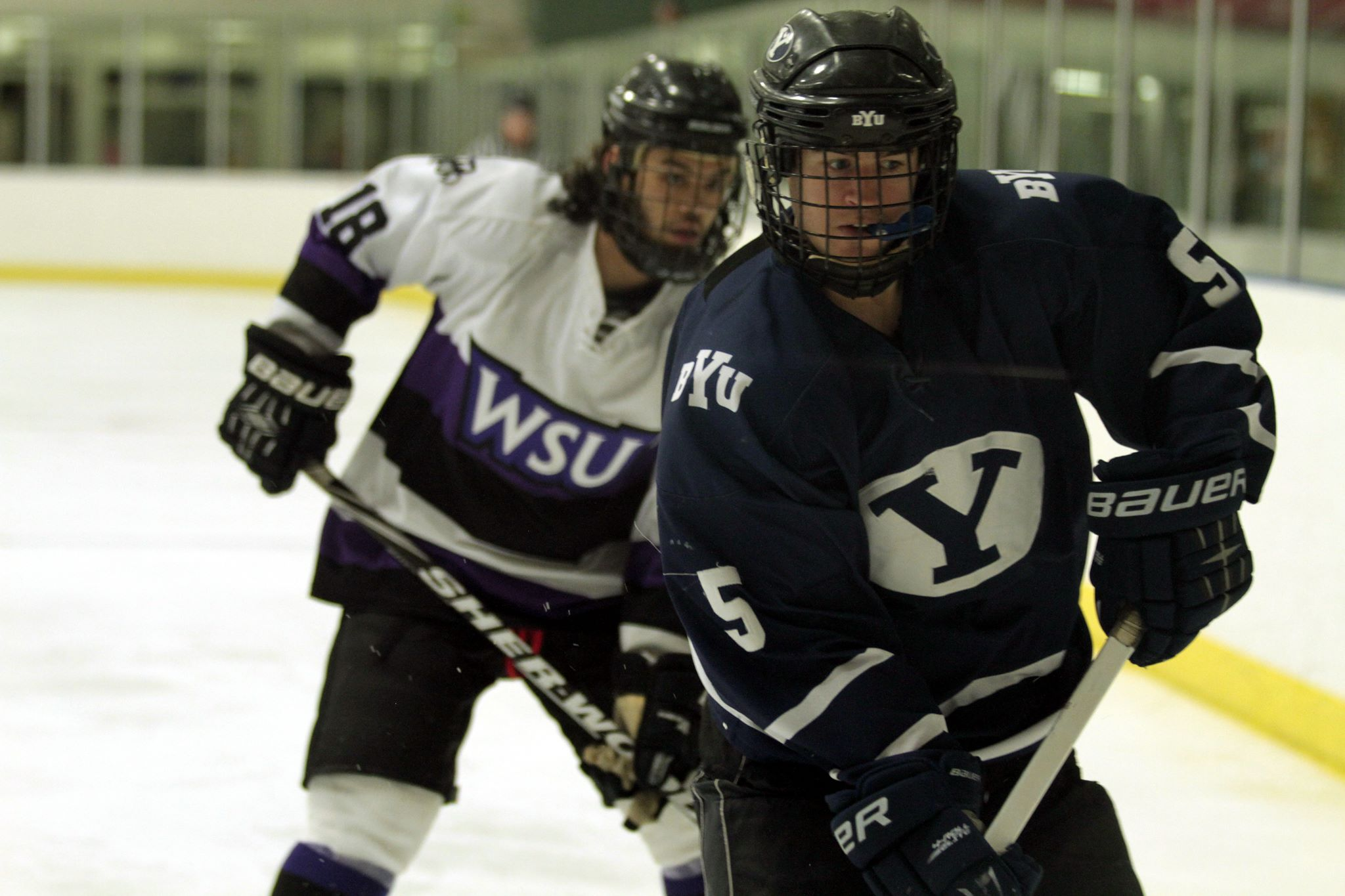 BYU's Josh Patrick (5) plays the puck against the boards as Weber State's Koda Coleman (18) closes in.